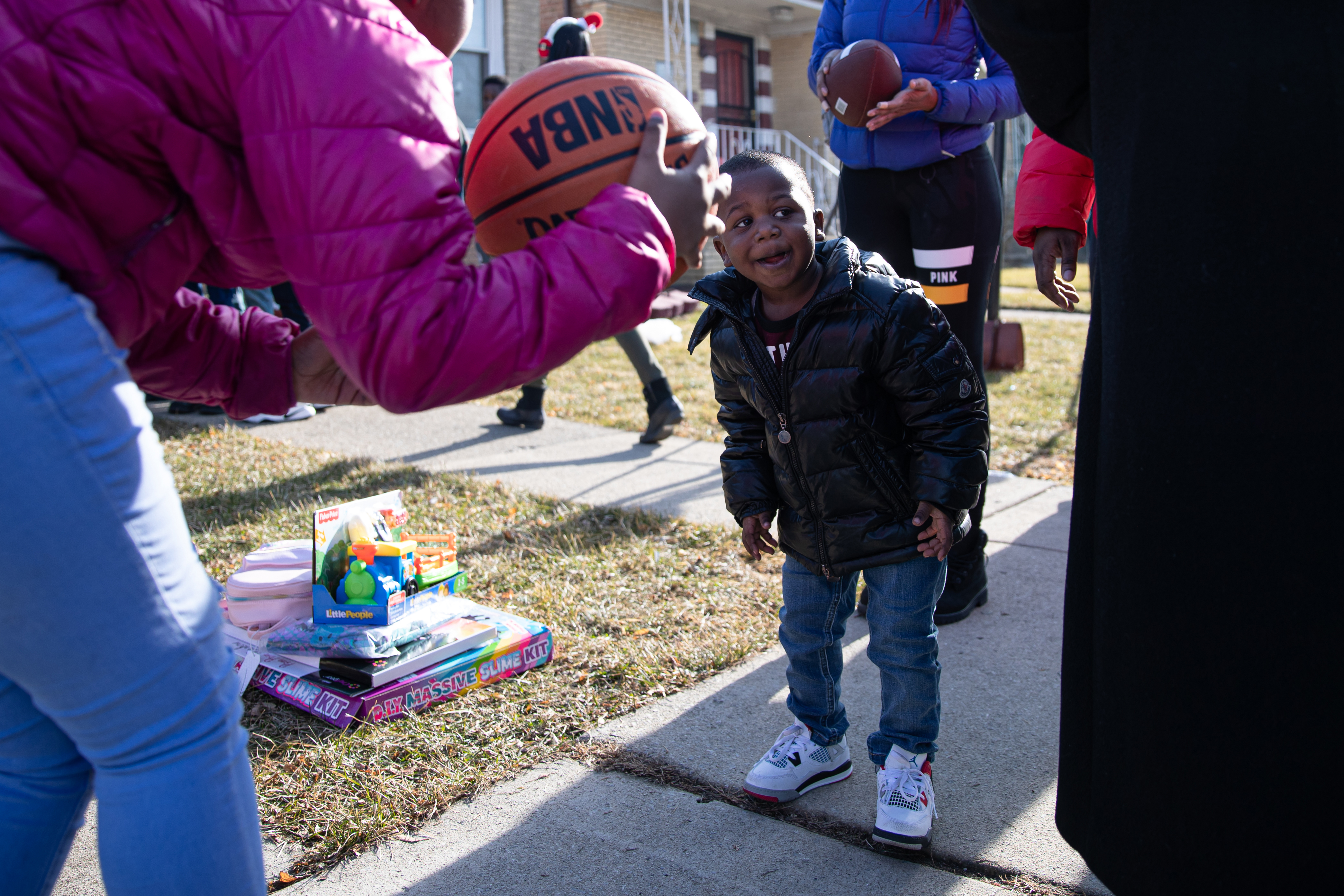 Gregory Martin reacts to Santa and presents during a Christmas Eve event to surprise the children of two mothers shot to death while working as peacemakers in Chicago.