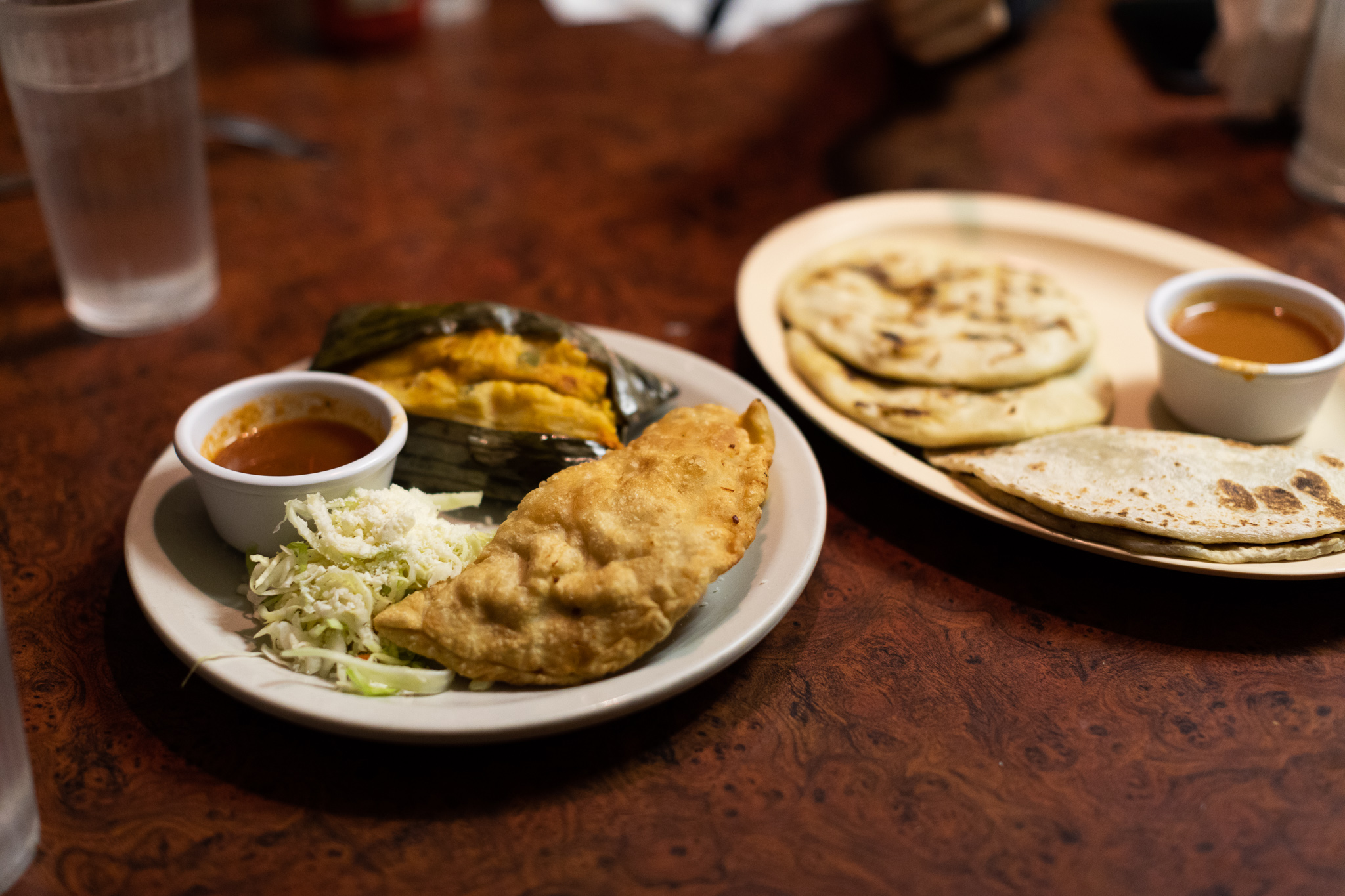 Tamales and pupusas on plates at Antojitos El Catracho.