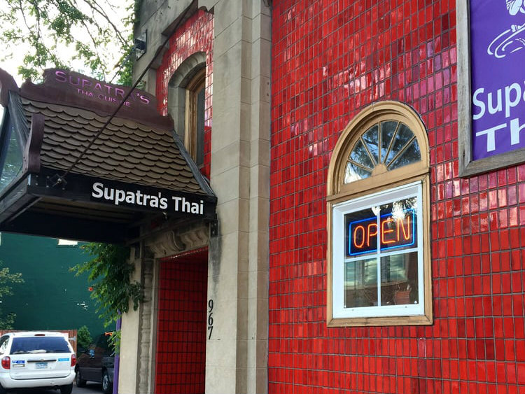 The shiny red tile exterior and purple sign outside Supatra's