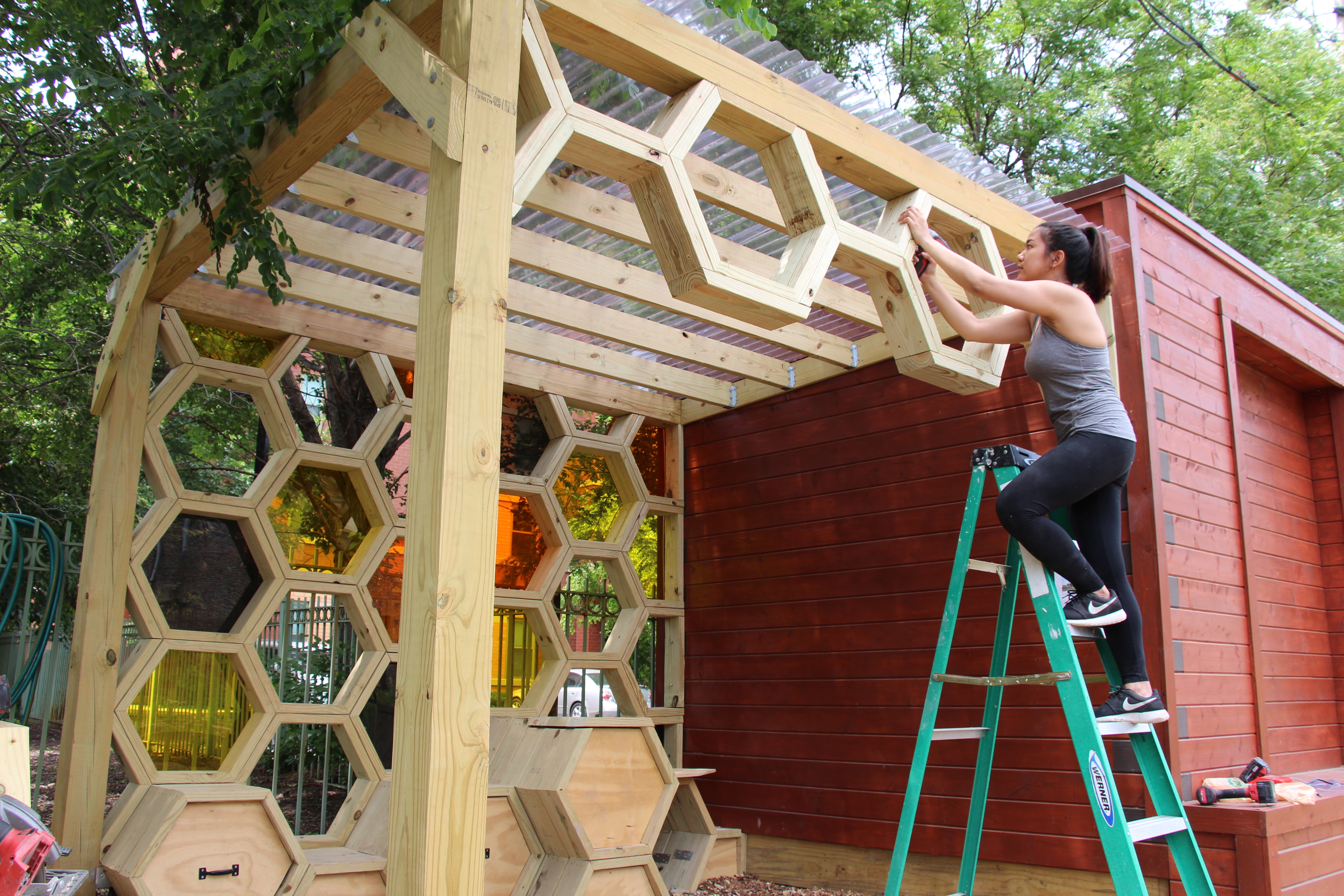 """Hsu Myat Aungworks on """"The Hive"""" at the El Paseo Community Garden in Pilsen."""