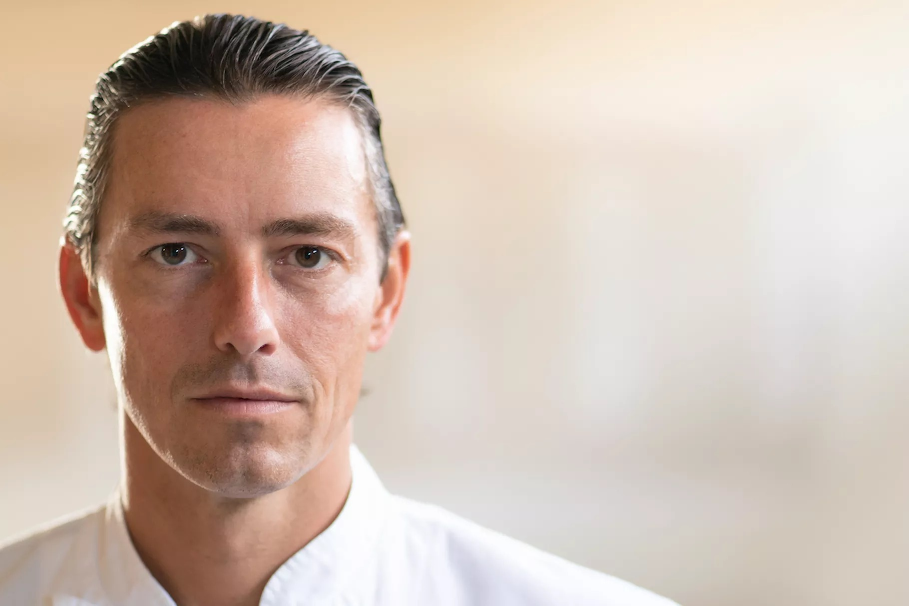 A portrait photo of Curtis Duffy, a white man, in a white chef's coat.