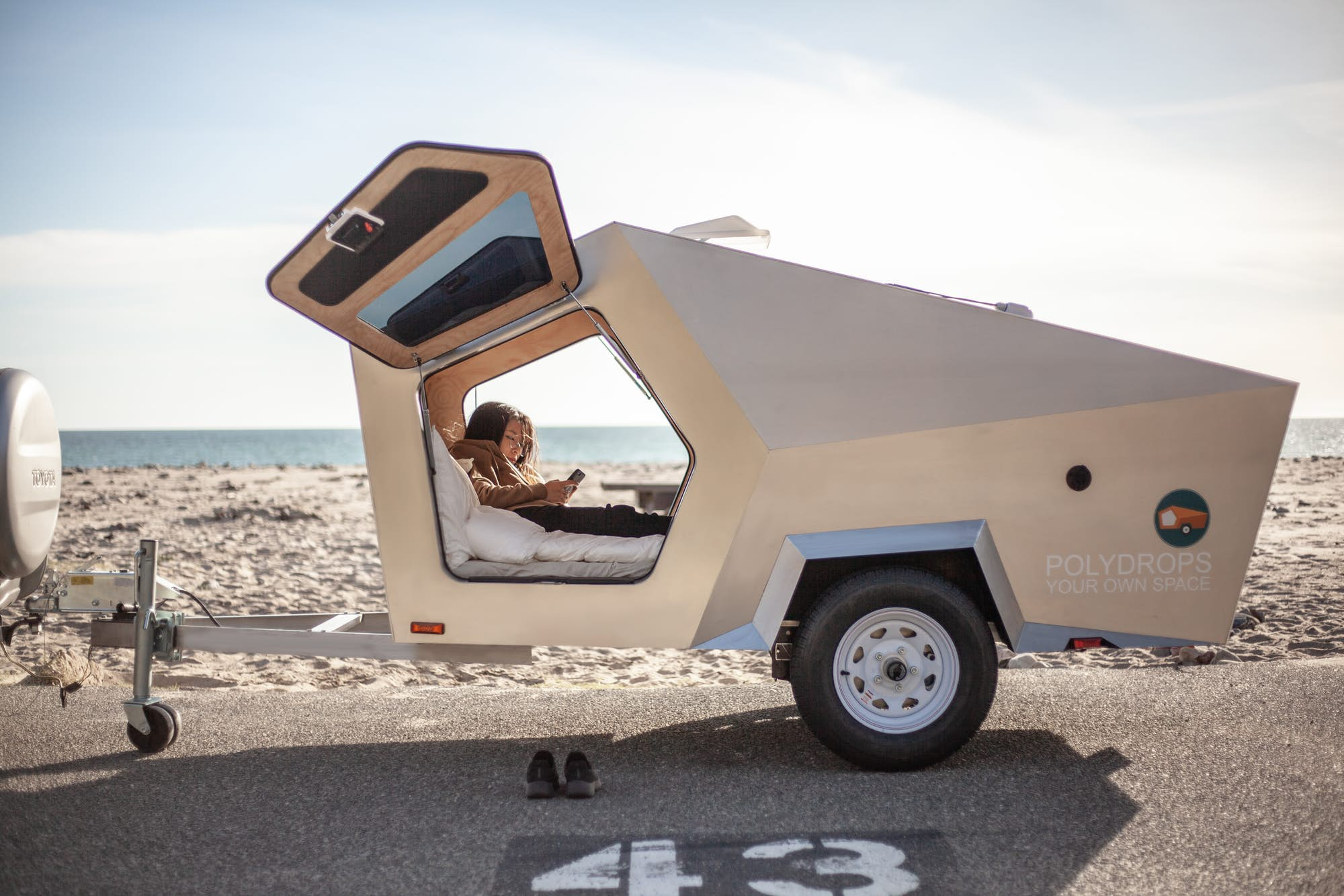 A white camper trailer in a desert. There are people in the trailer lounging on a bed.