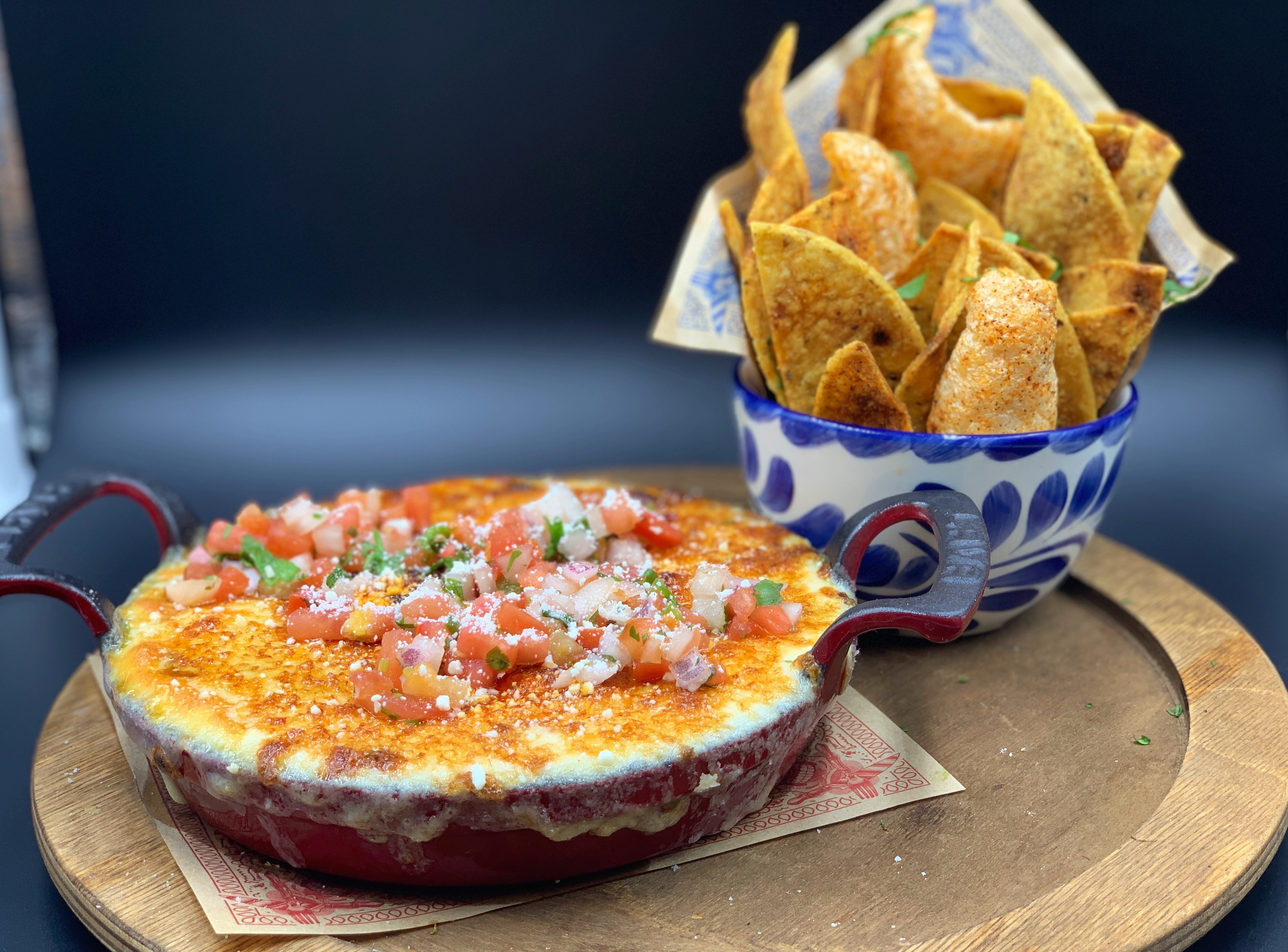 Queso fundido topped with chopped tomatoes and more sits in a small red pan. There's a blue and white bowl of tortilla chips to the right, and both vessels sit on a wooden tray.
