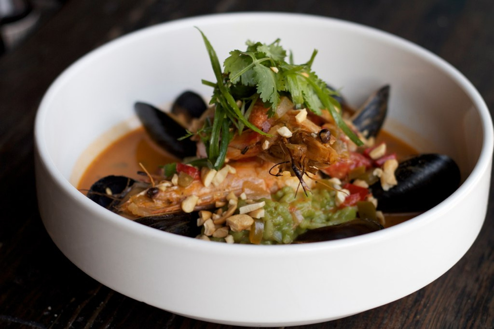 A white bowl filled with prawns, mussels, and broth.