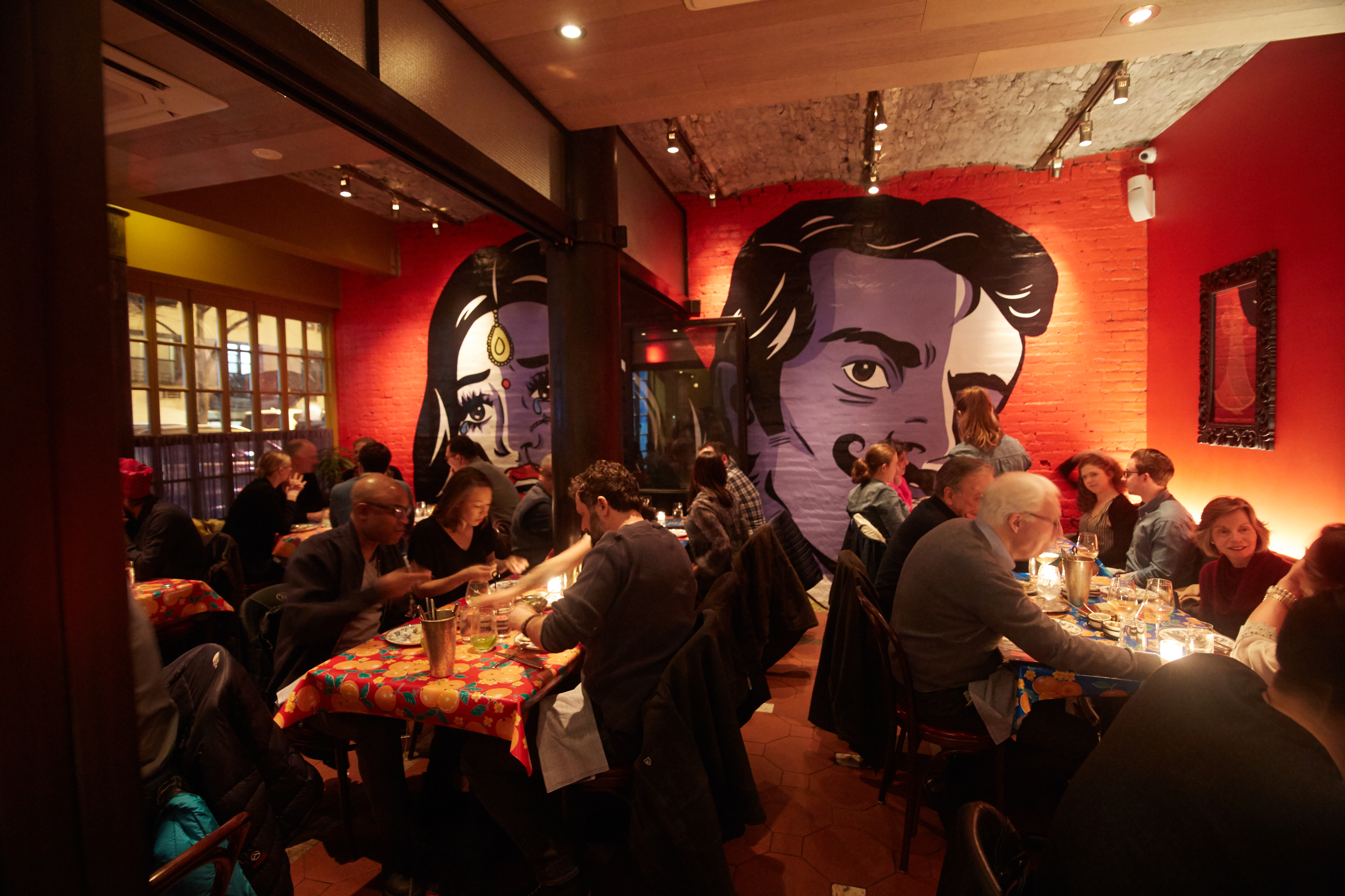 Bombay Bread Bar's dining room, with red walls and a mural of people in the back.