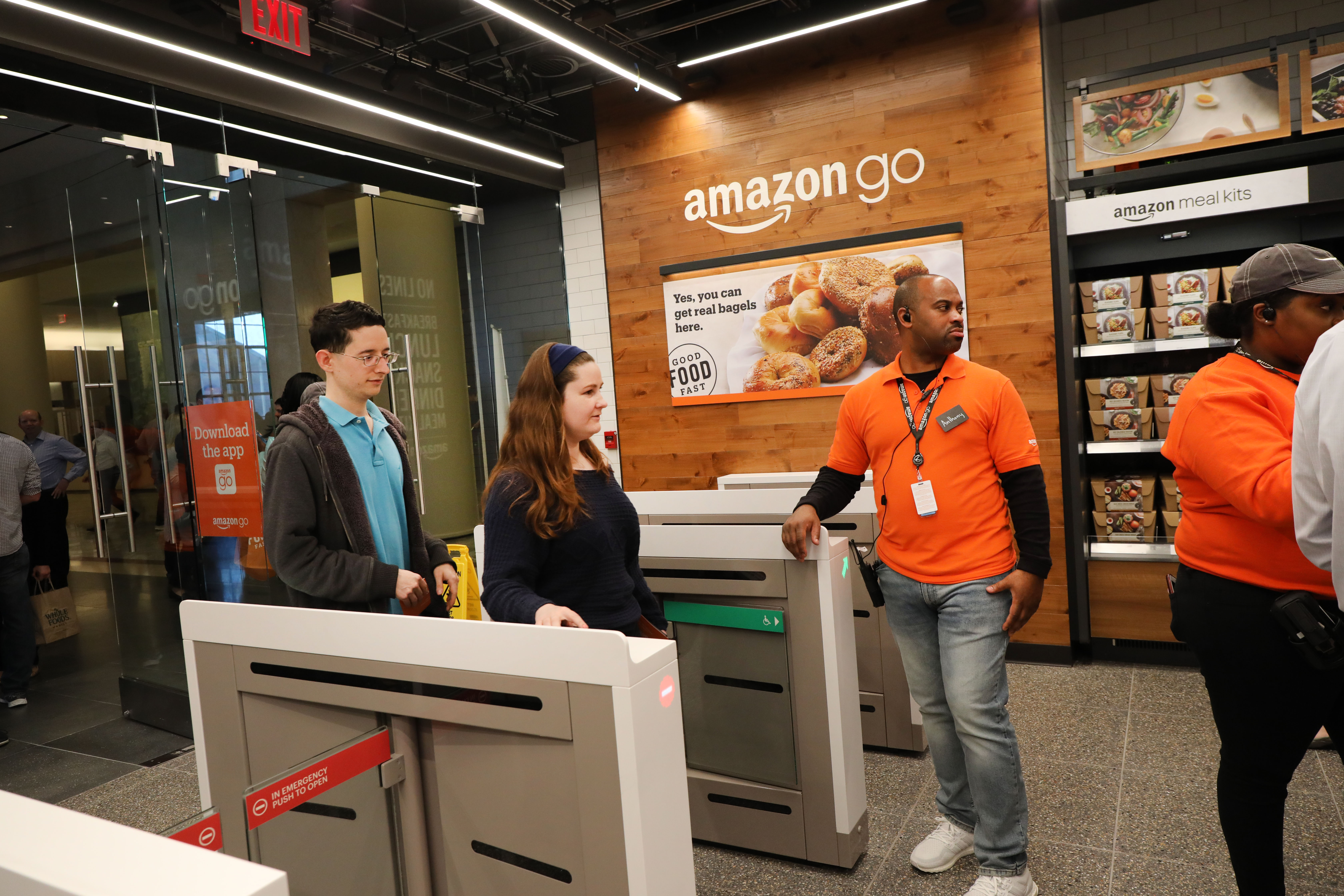 Customers walk through an Amazon Go store's entry gates.