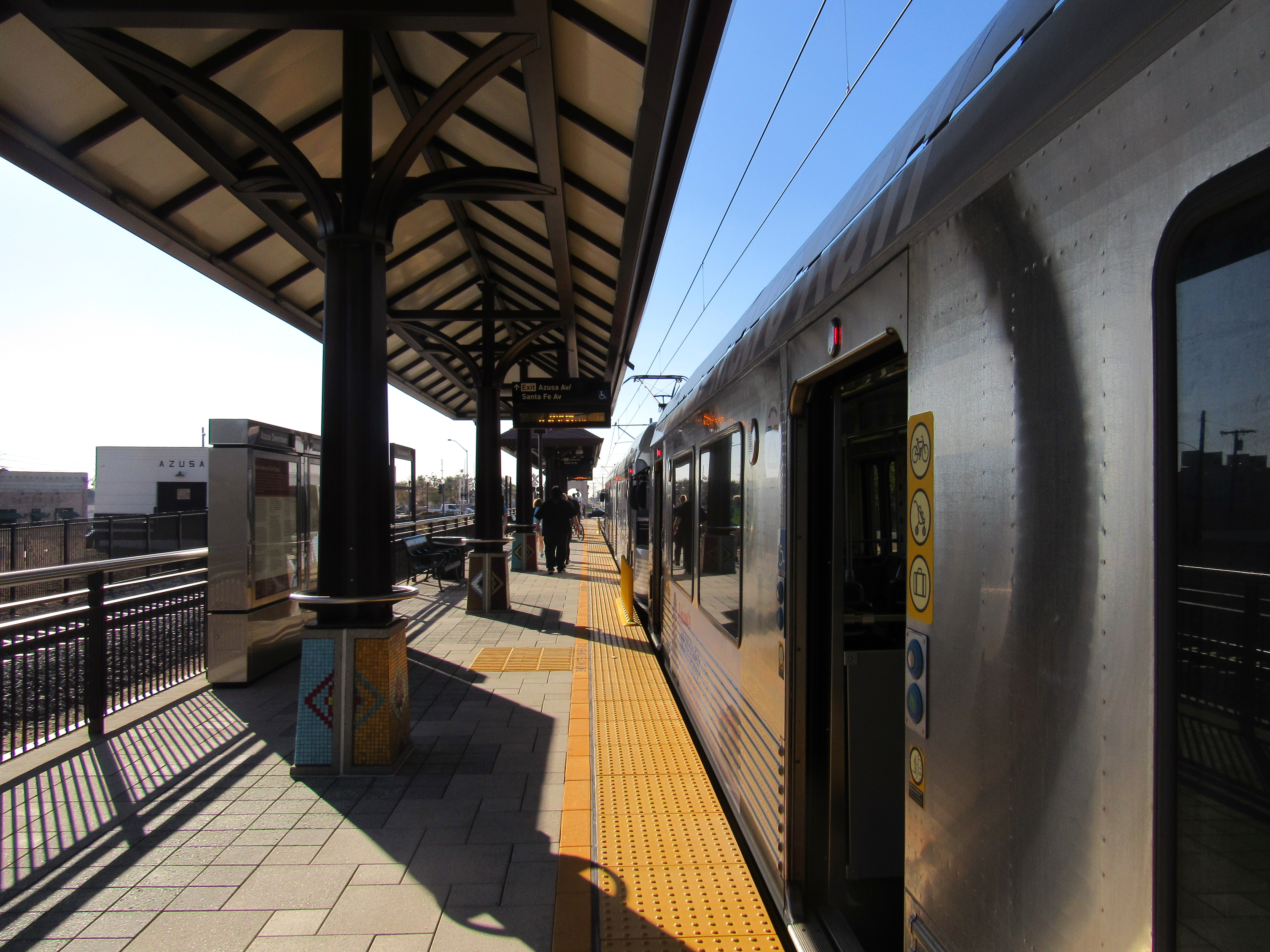 A silver train at a platform with doors open