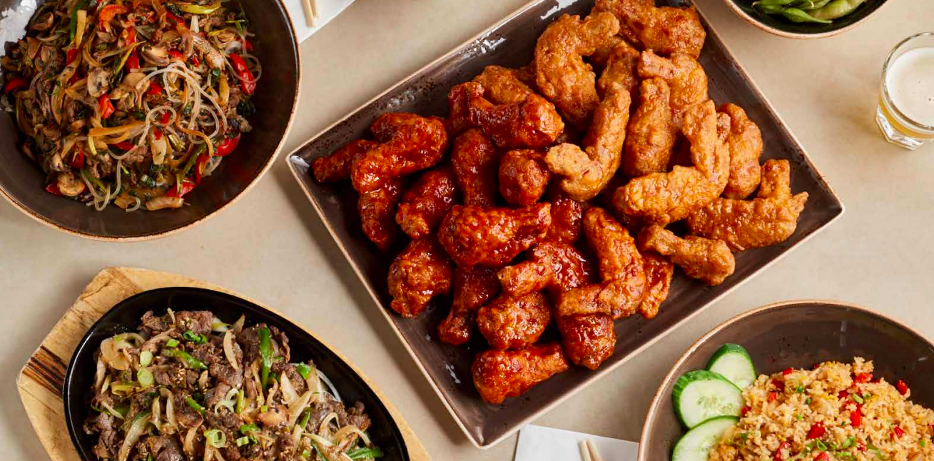 A picture of Korean fried chicken wings, japchae, and other dishes from Bonchon