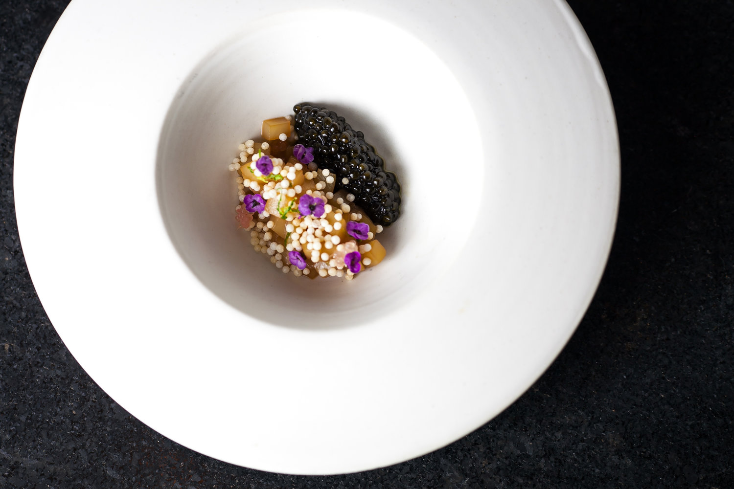 A large round white bowl with caviar and purple flowers