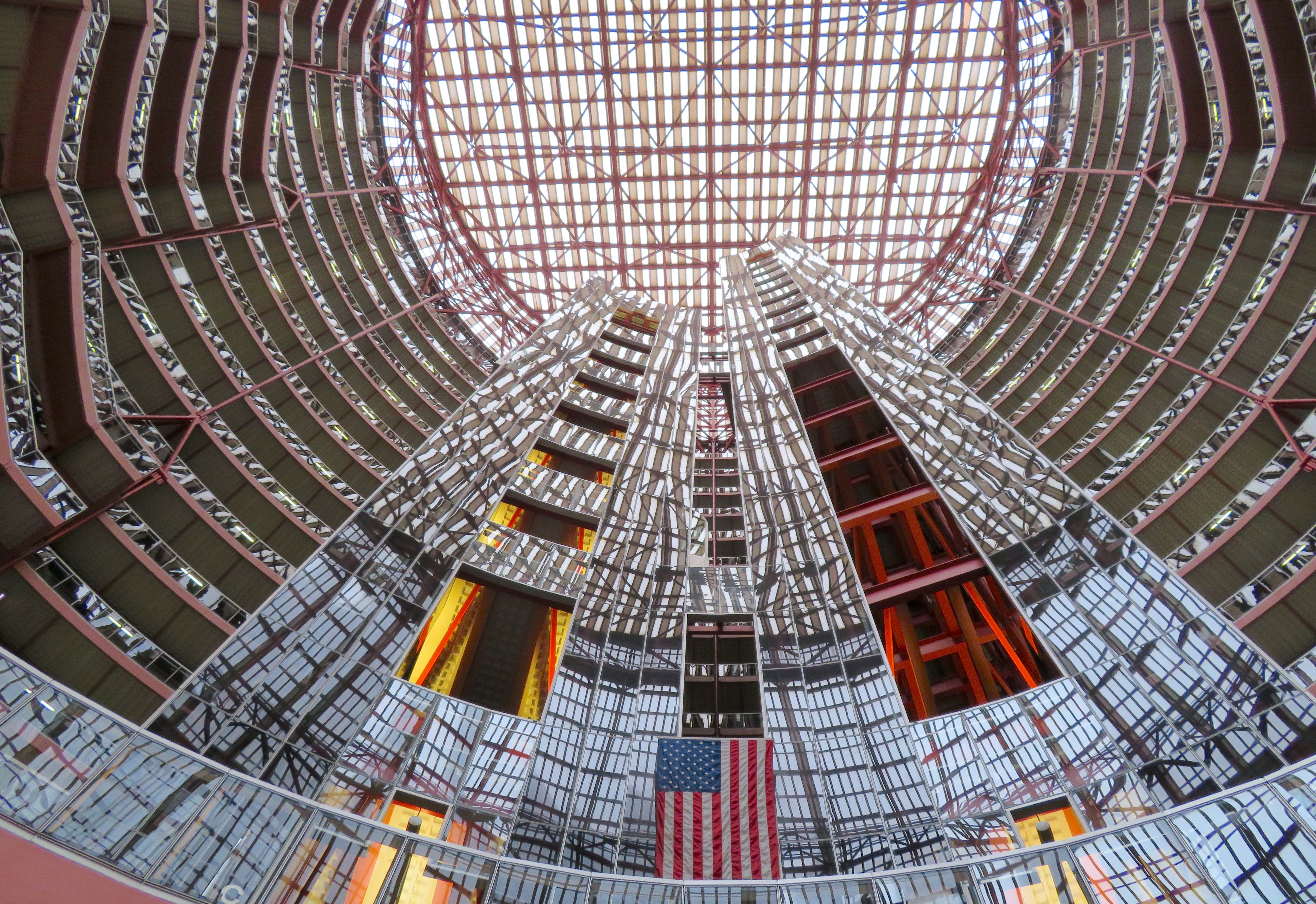 A view upward at a massive circular Thompson Center atrium ringed with offices. Glass elevator shafts rise in the center and reflect the surrounding architecture.