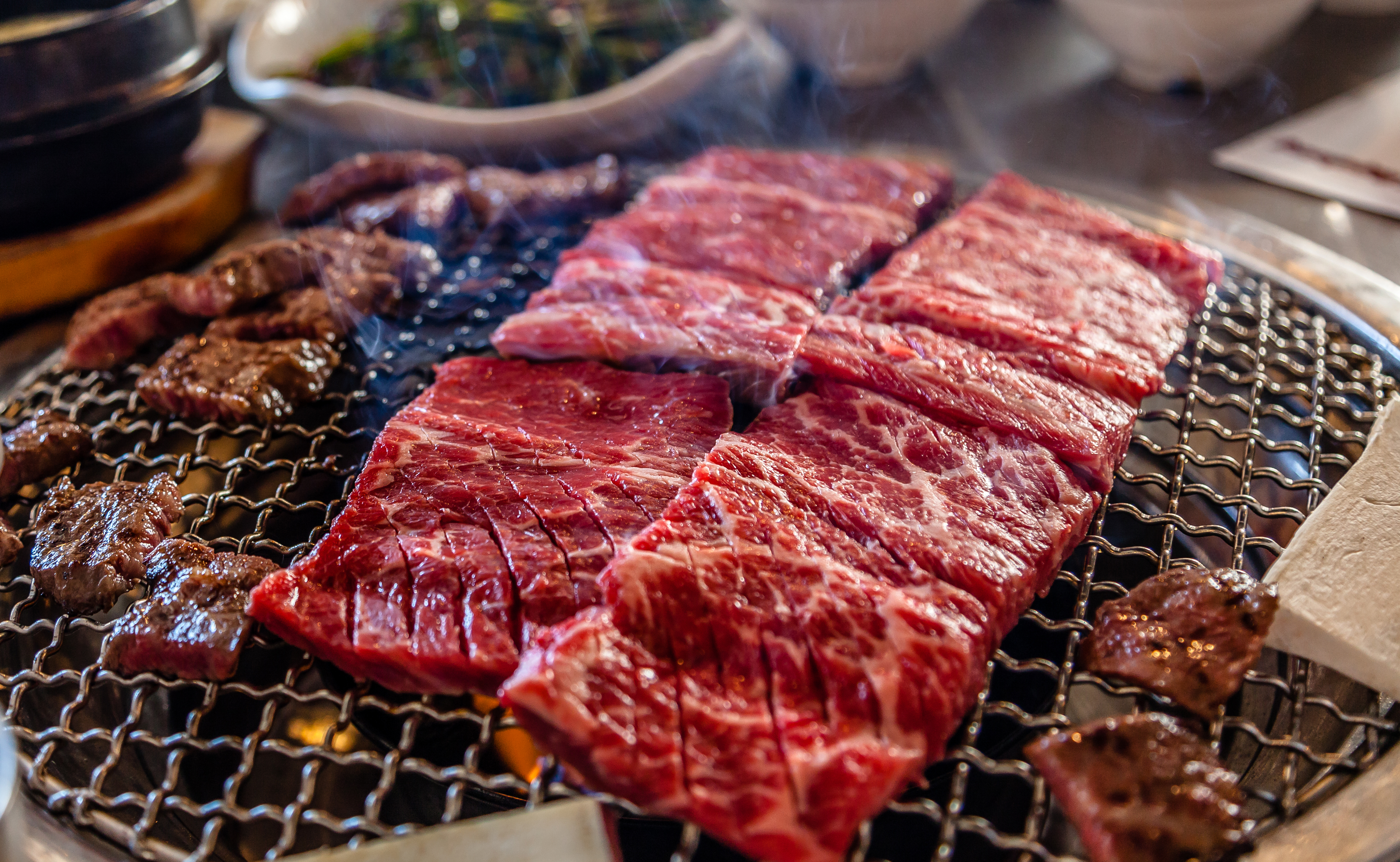Raw beef cooking on a small grill.