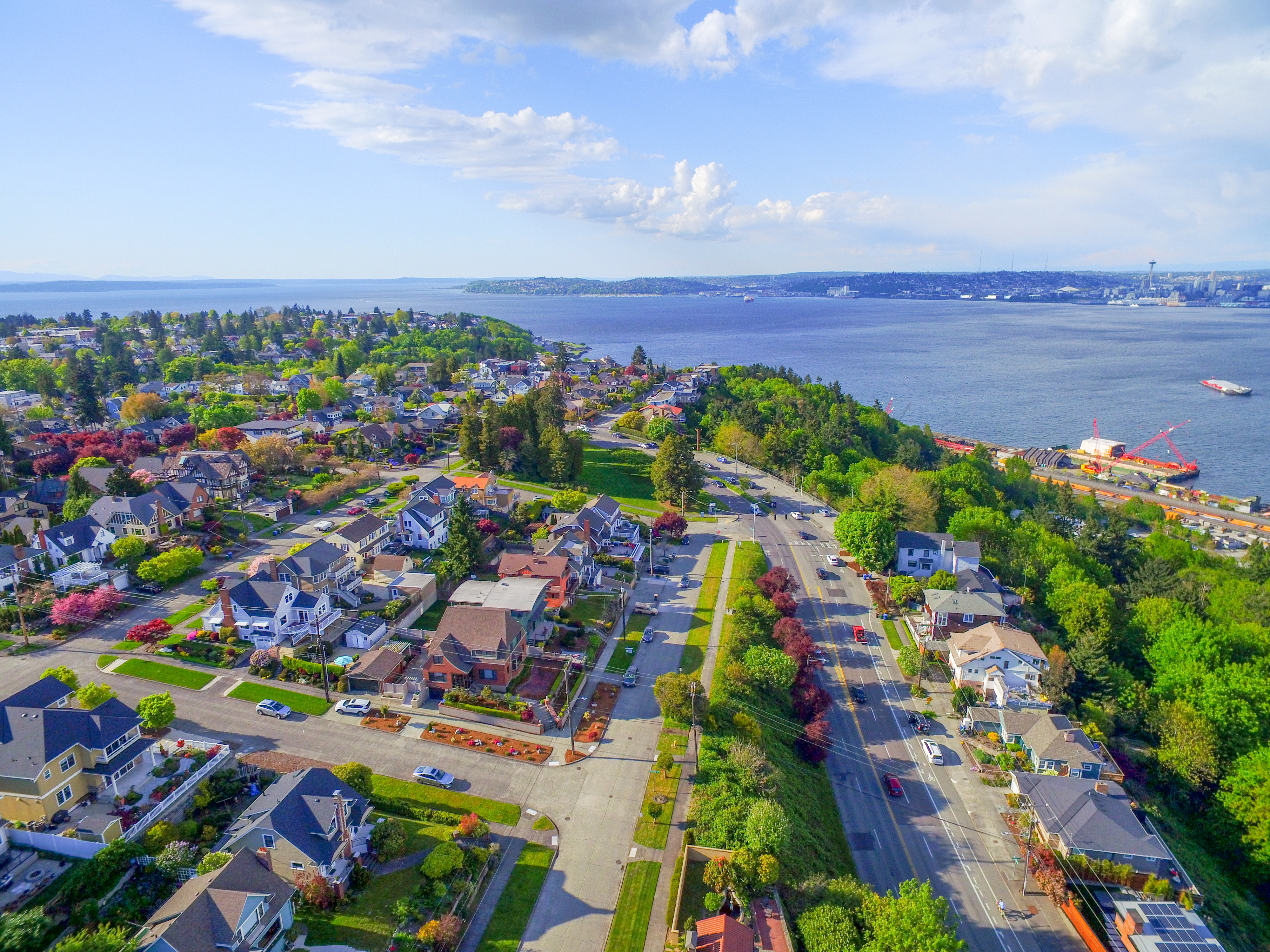 An aerial view of West Seattle and the Puget Sound waterfront on a clear, sunny day.