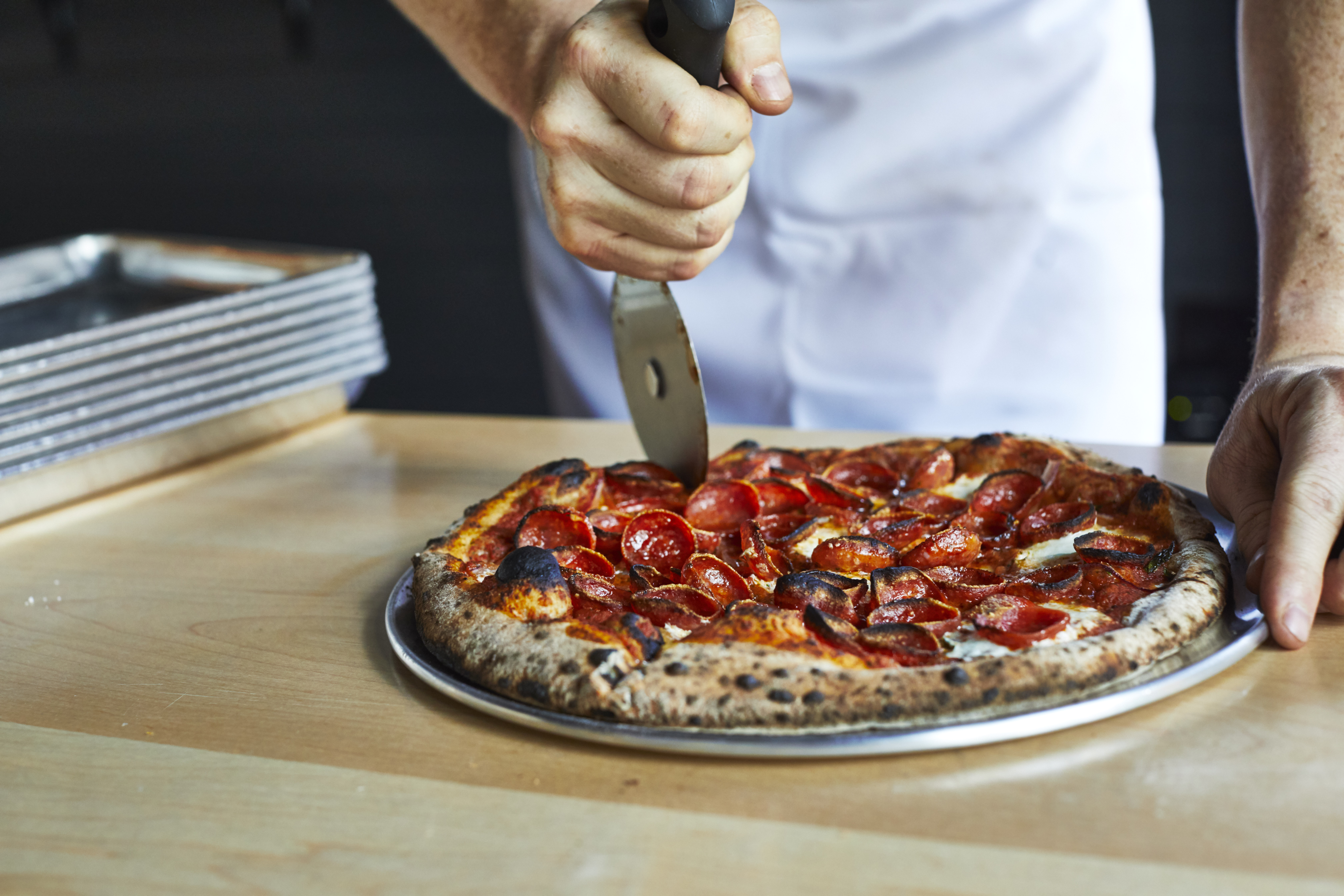 a man's hand slices a pepperoni topped pizza on the counter