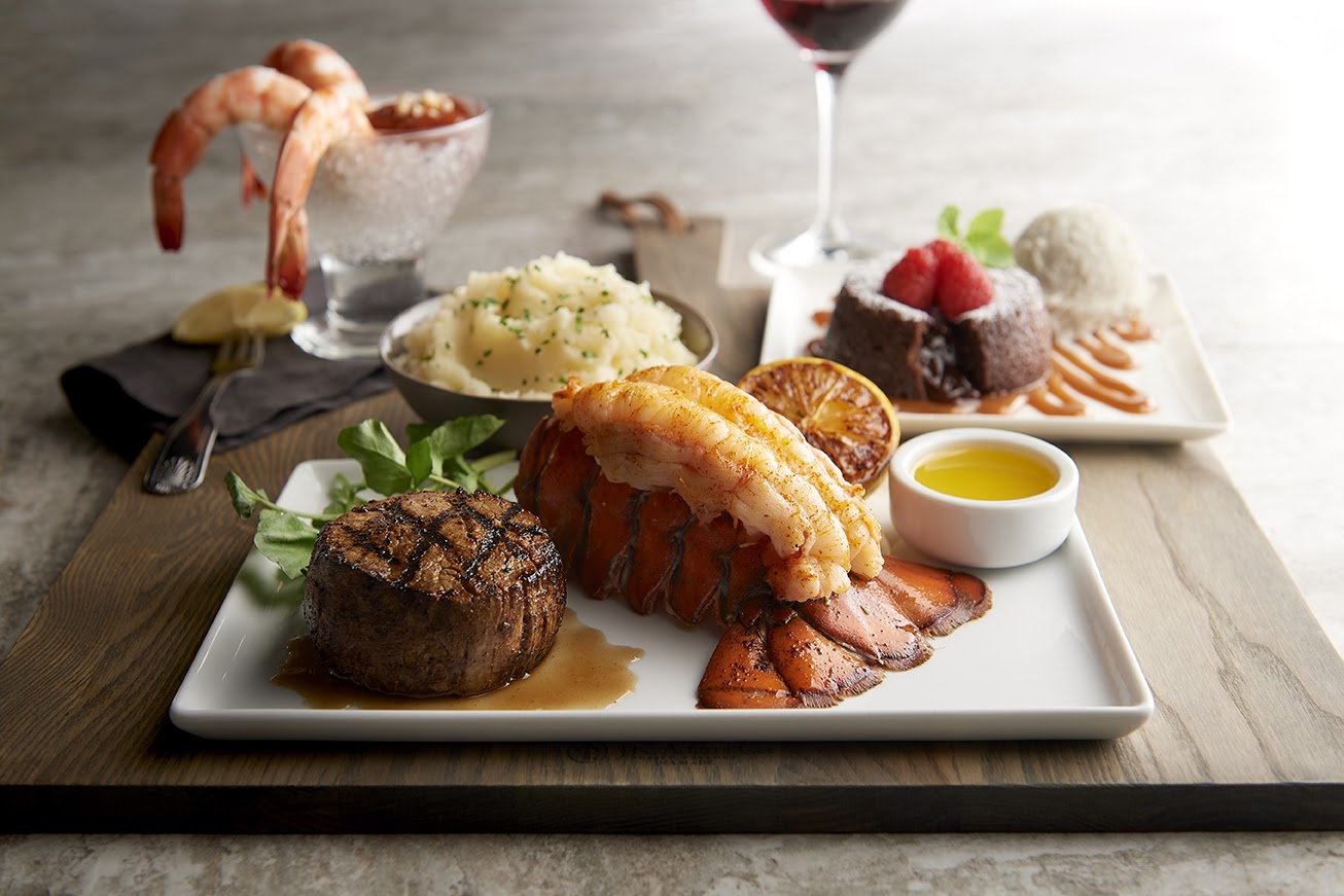A white plate holds a steak and lobster.