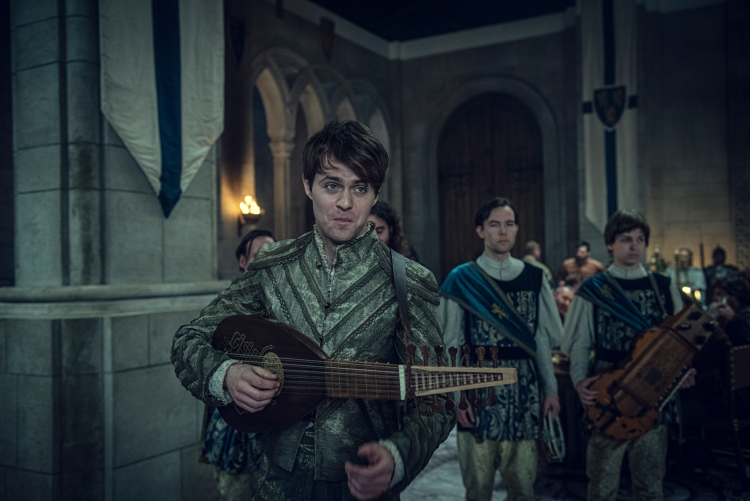 a young dark-haired man holding a lute walks into a banquet hall in The Witcher