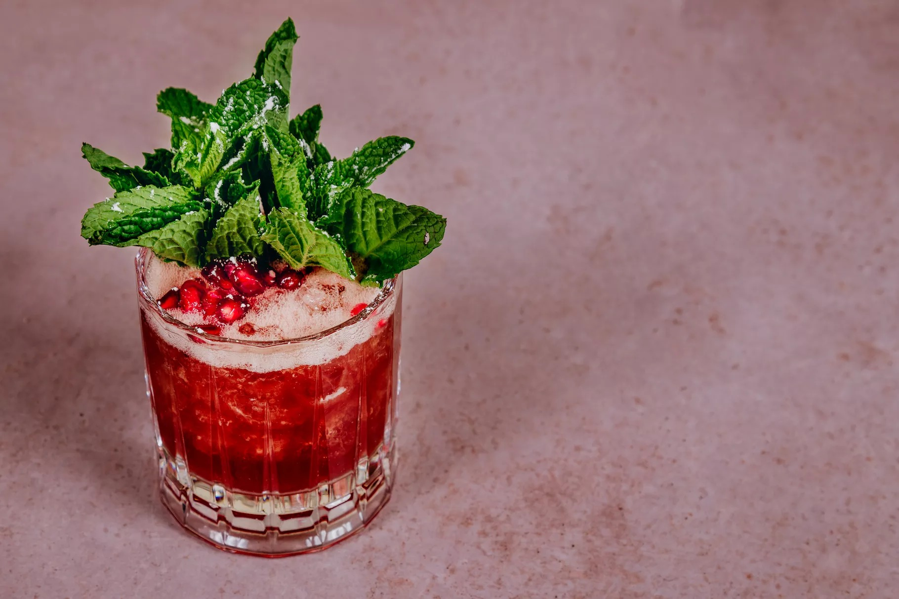 A red cocktail with pomegranate seeds and a green shrub garnish.