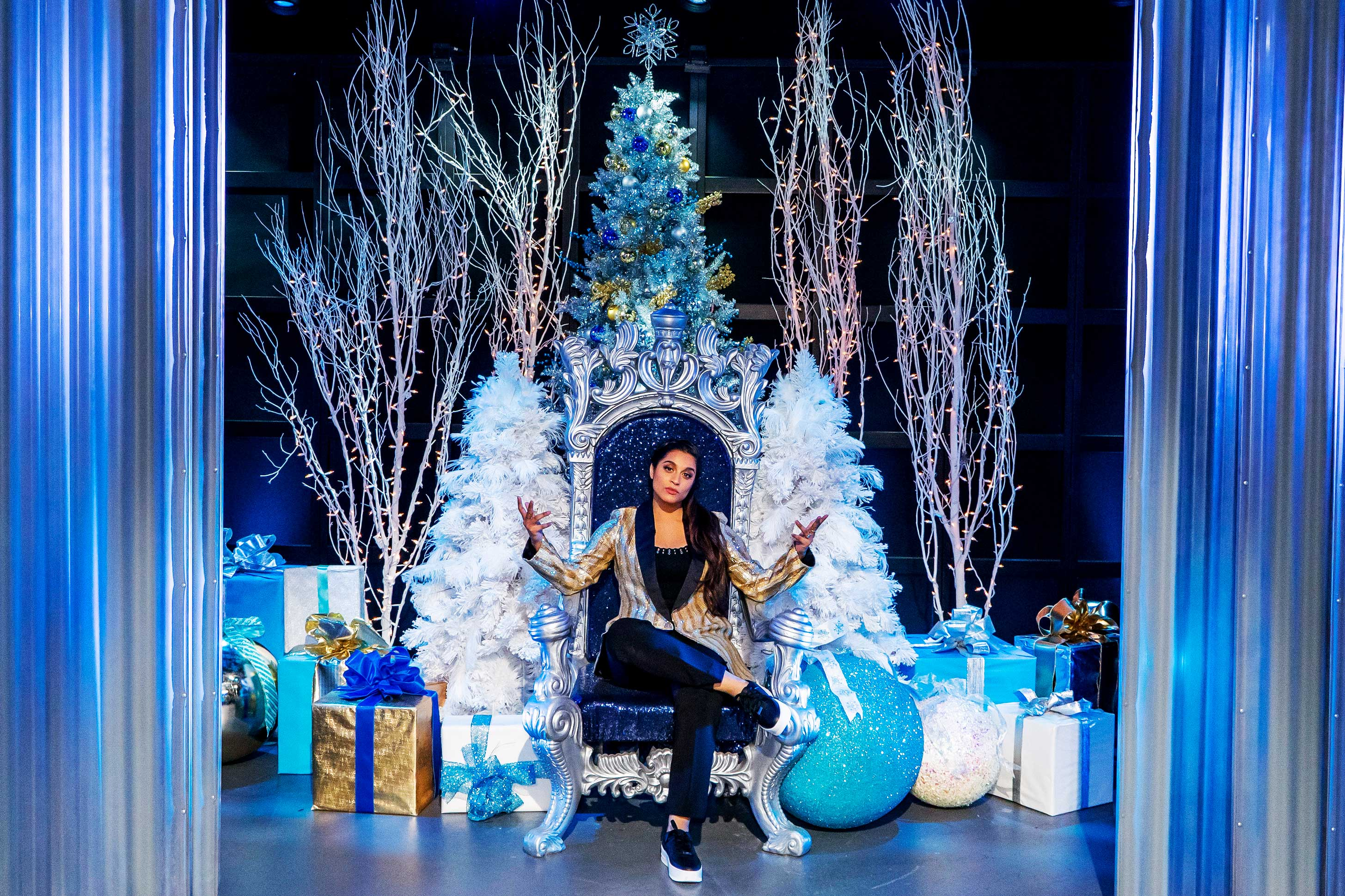 YouTube personality Lilly Singh sits onstage on a throne chair surrounded by Christmas decorations.