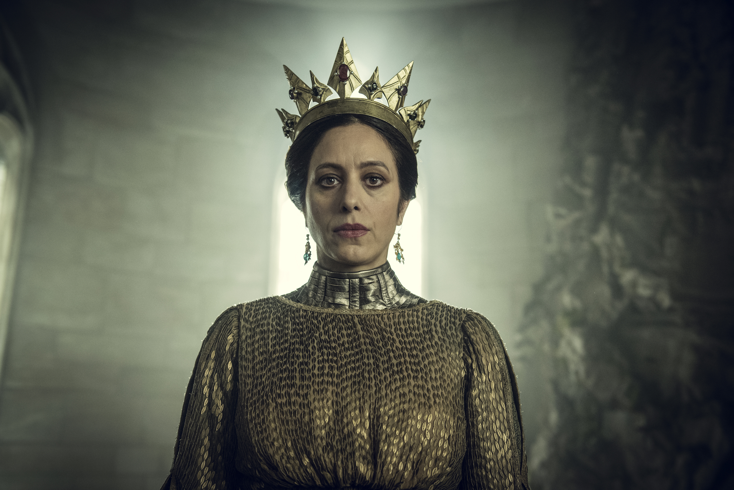 Queen Calanthe, a dark-haired woman wearing a golden dress and a golden crown, framed by light behind her in The Witcher