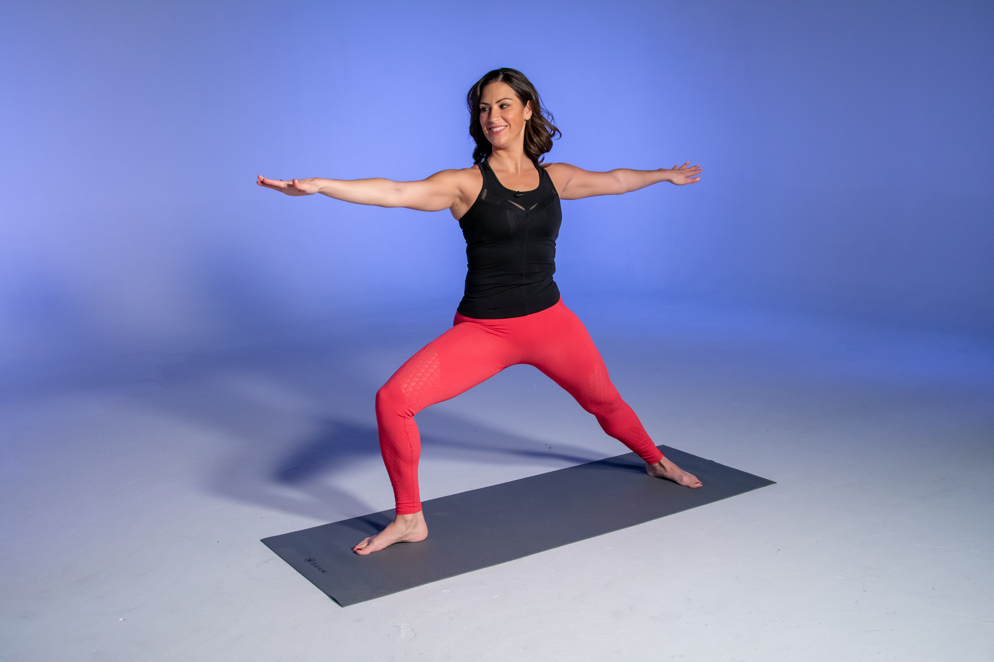 Health and fitness expert Stephanie Mansour in yoga pose Warrior II, the first step in working towards Bird of Paradise.
