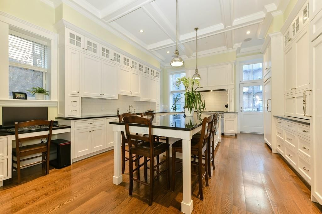A sizable kitchen with lots of cabinetry and an island with chairs around it.