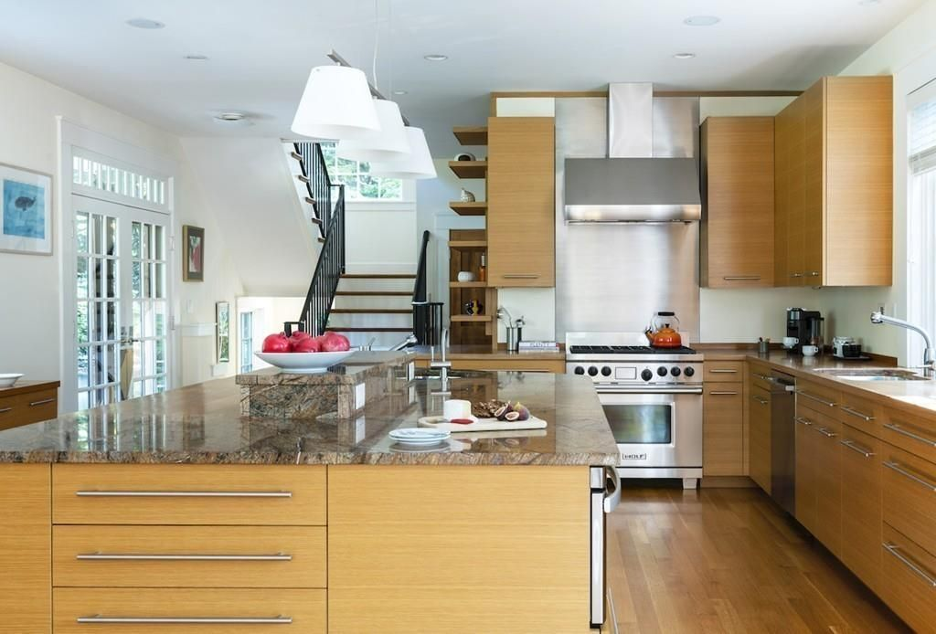 A modern, spacious kitchen with an island a stairwell leading into it.