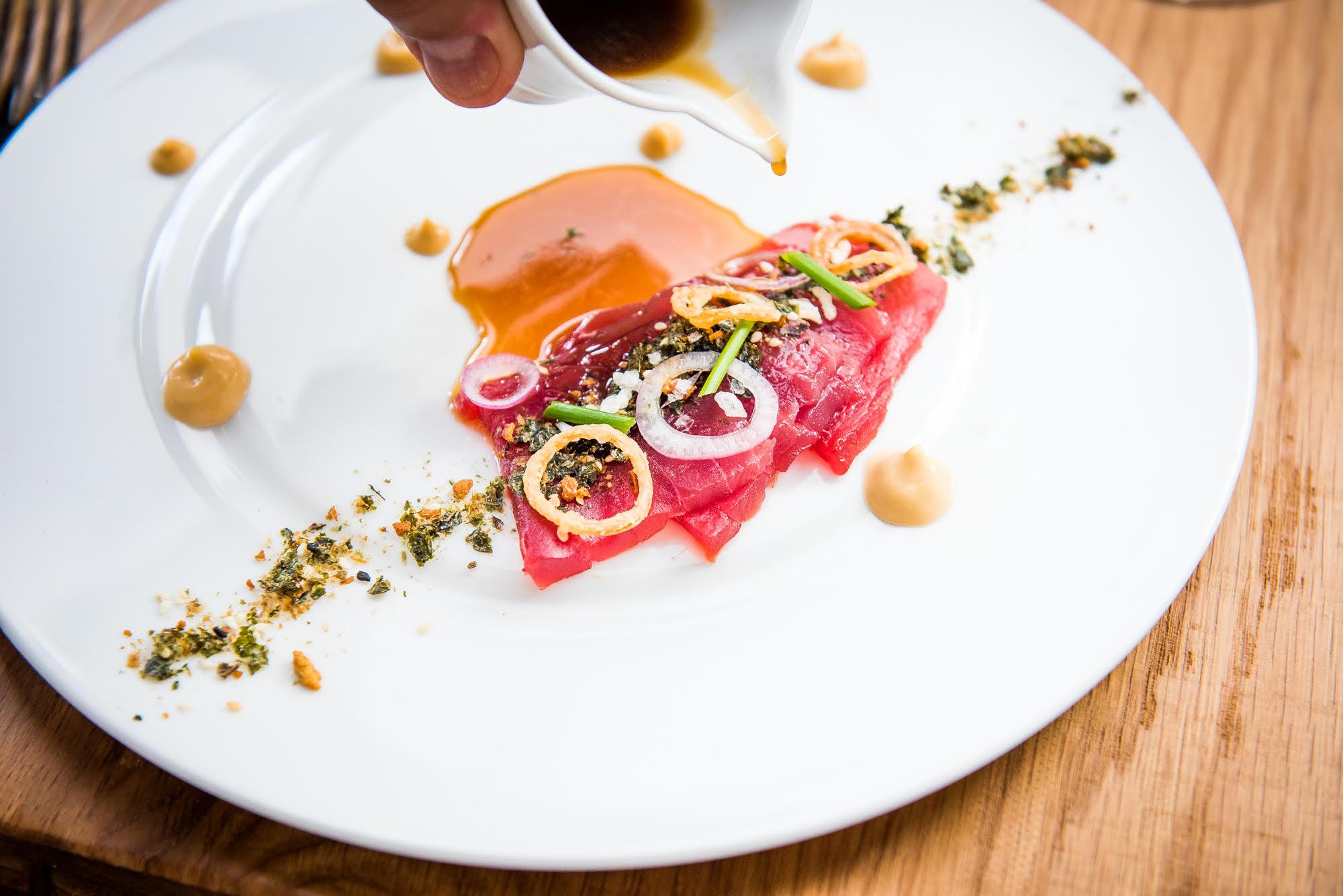 Tuna crudo at Gravitas, on a white plate flecked with edible flour