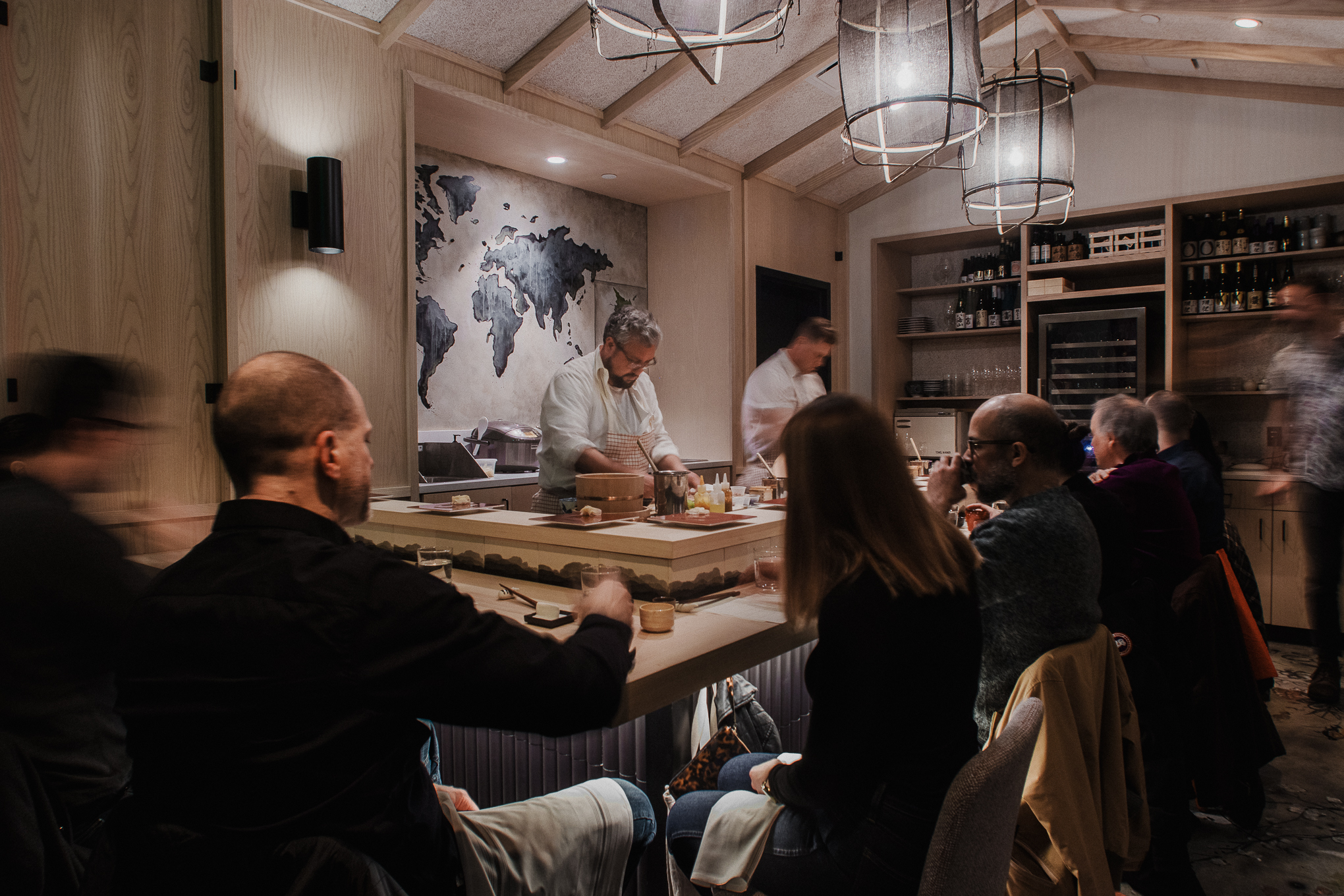 Patrons sit at a small sushi bar with two chefs behind the bar