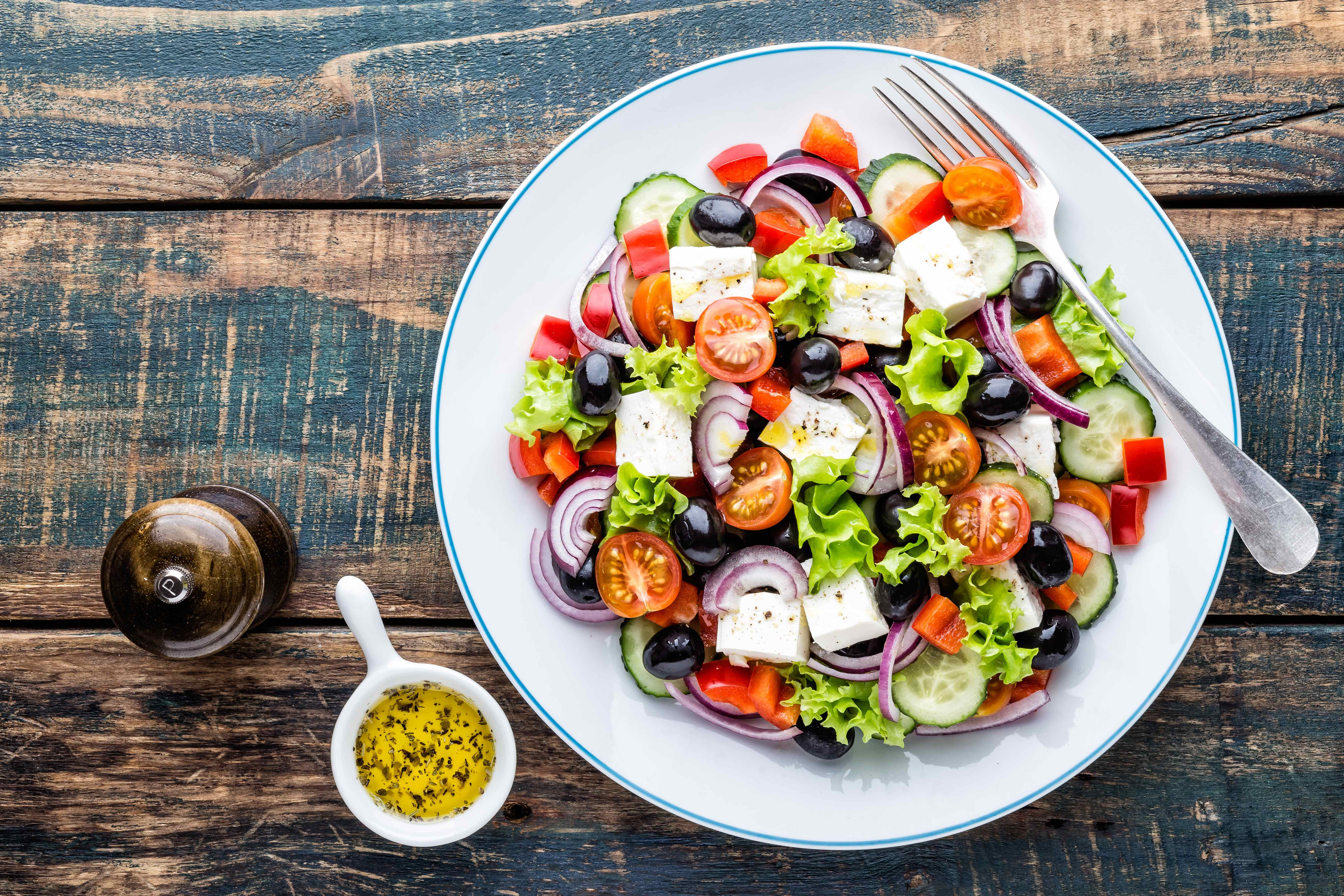 greek salad with pepper shaker and container of spices