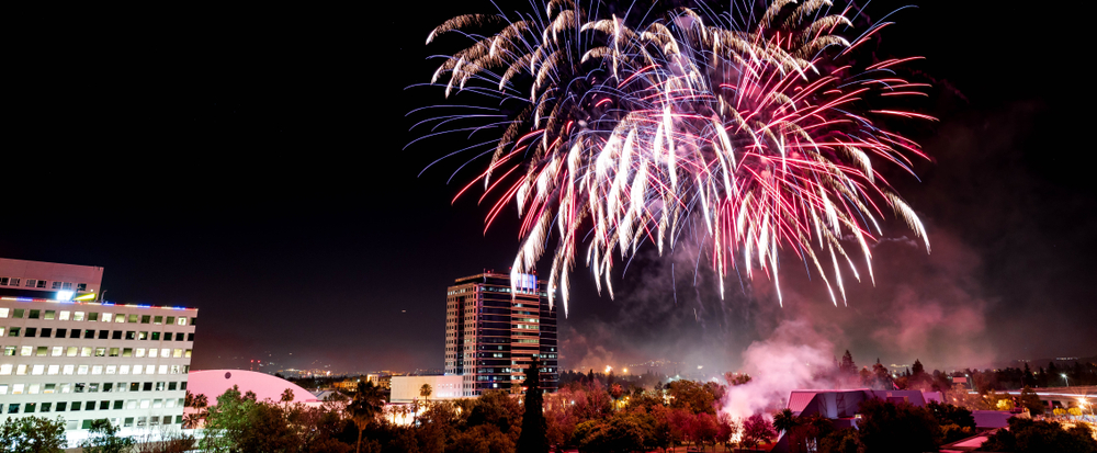 White, red, and purple fireworks exploding over San Jose.