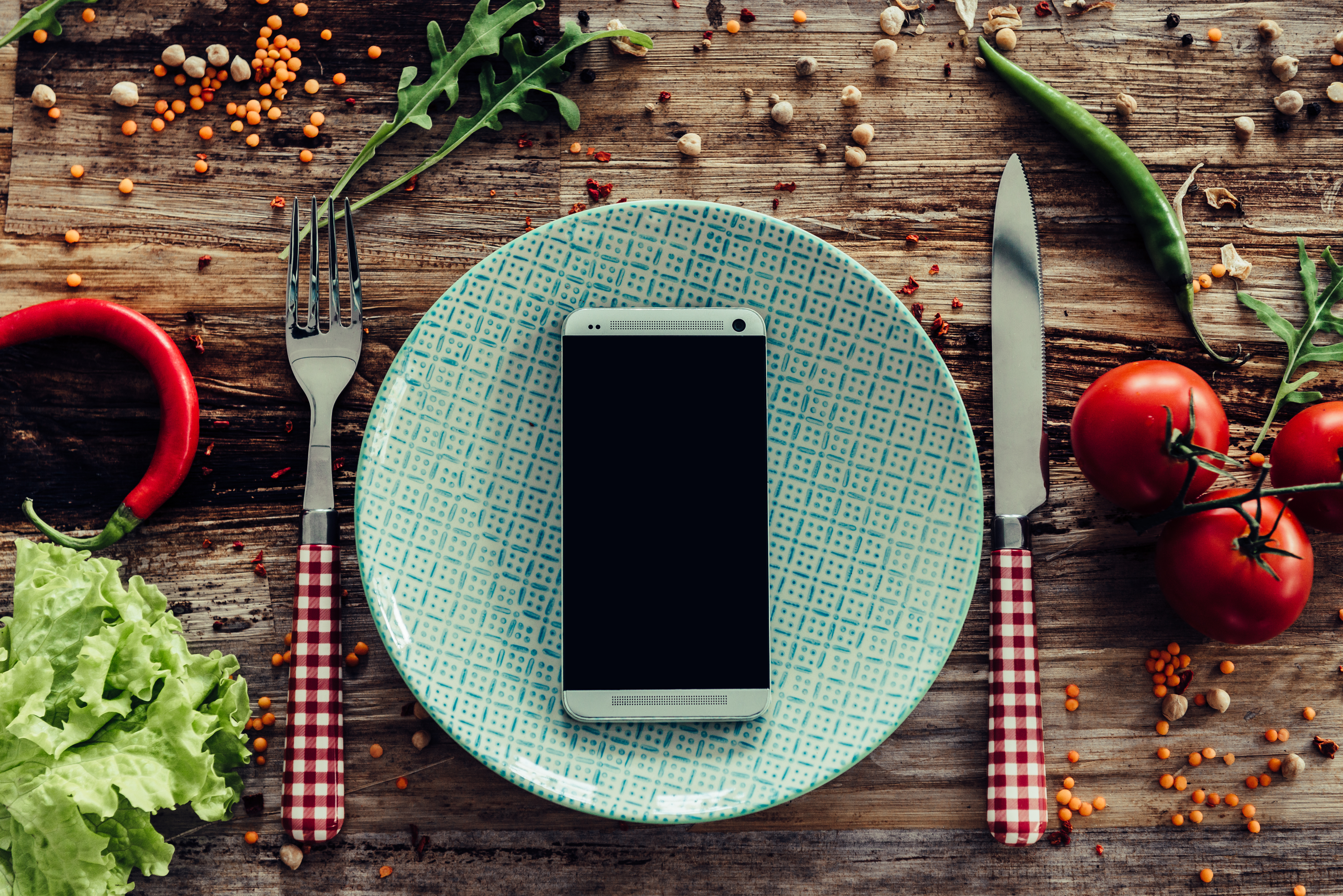 A cell phone on a white plate with a knife and fork on either side.
