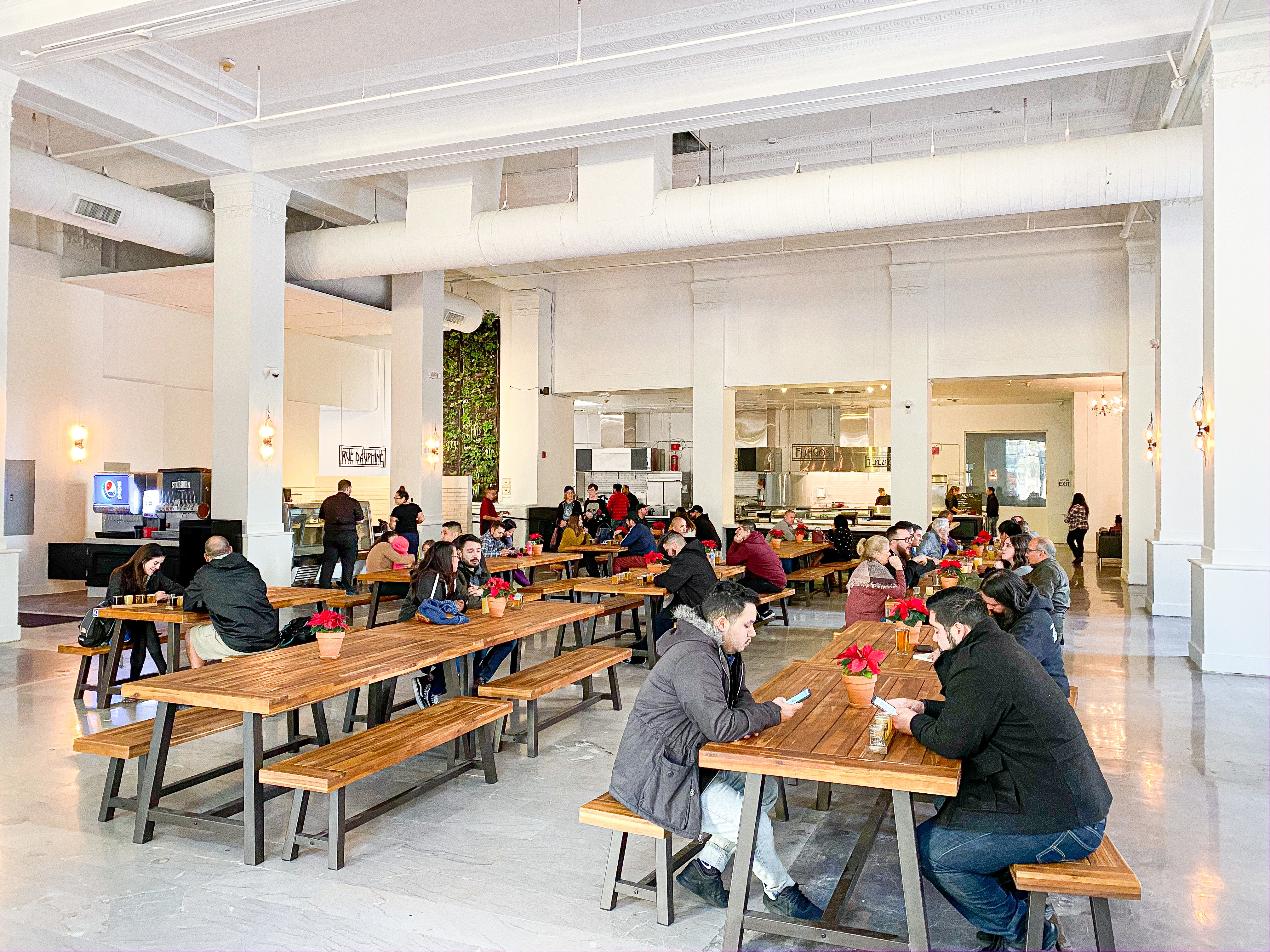 A bunch of diners eat at long communal tables inside a tall building.