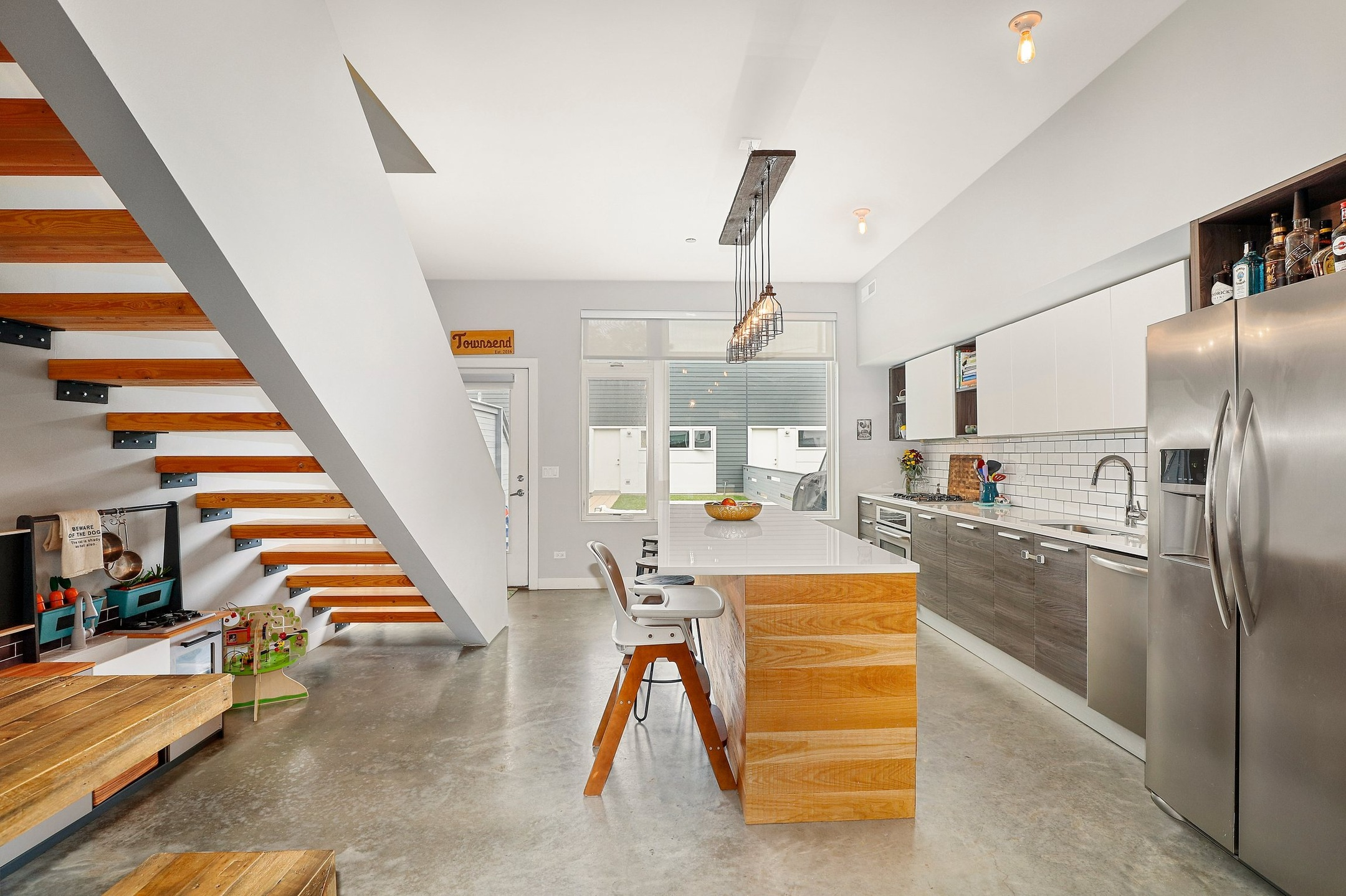 An open kitchen with a floating staircase leading to a second level. There's a wood and quartz island, gray cabinets, and stainless appliances.