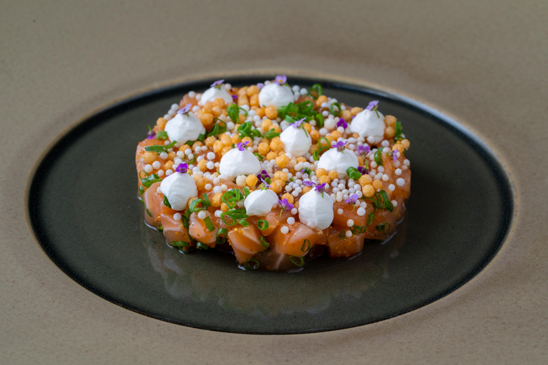 A bright sashimi dish that's shaped like a disc.