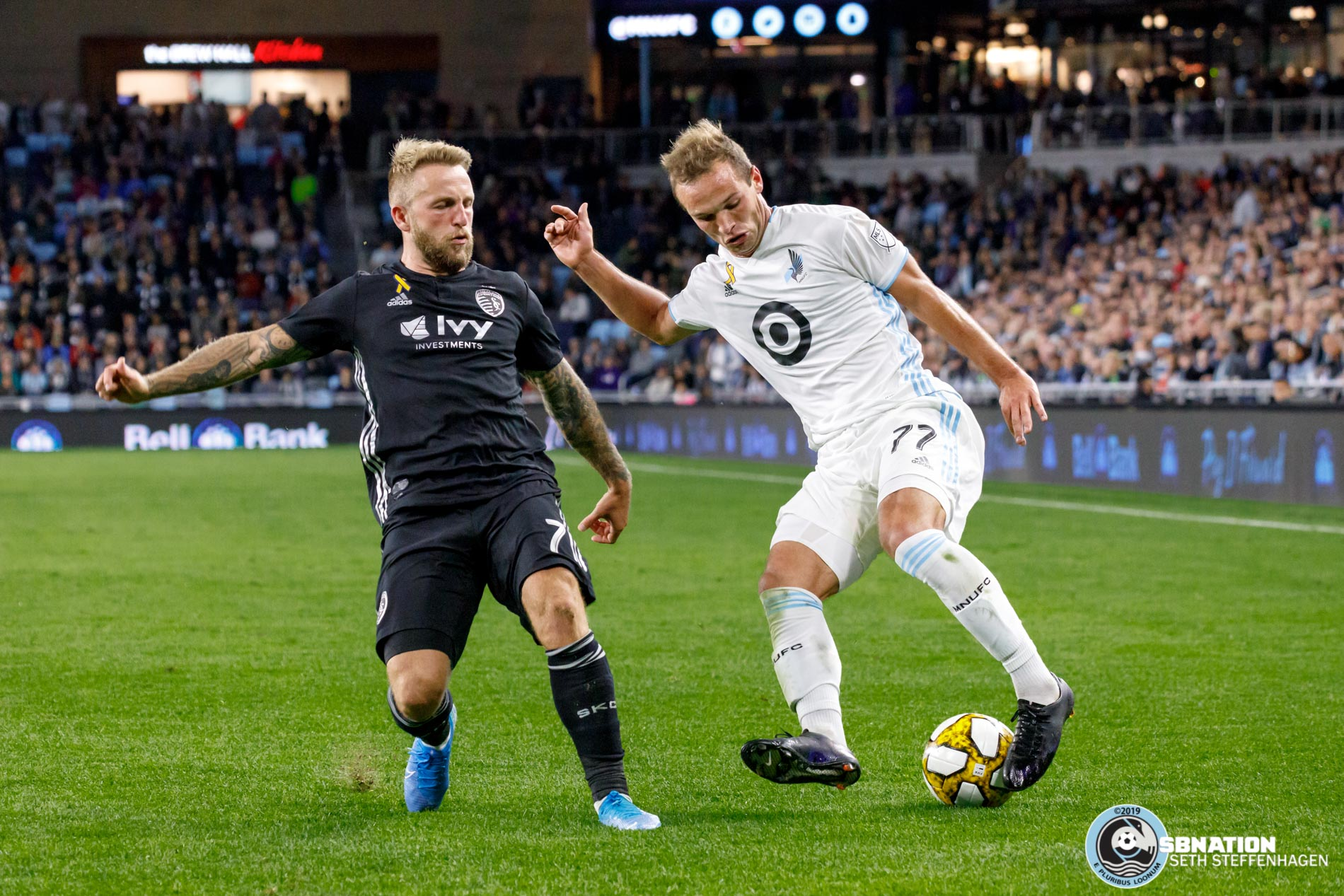 September 25, 2019 - Saint Paul, Minnesota, United States - Minnesota United defender Chase Gasper (77) dribbles the ball by Sporting KC forward Johnny Russell (7) during a match at Allianz Field.