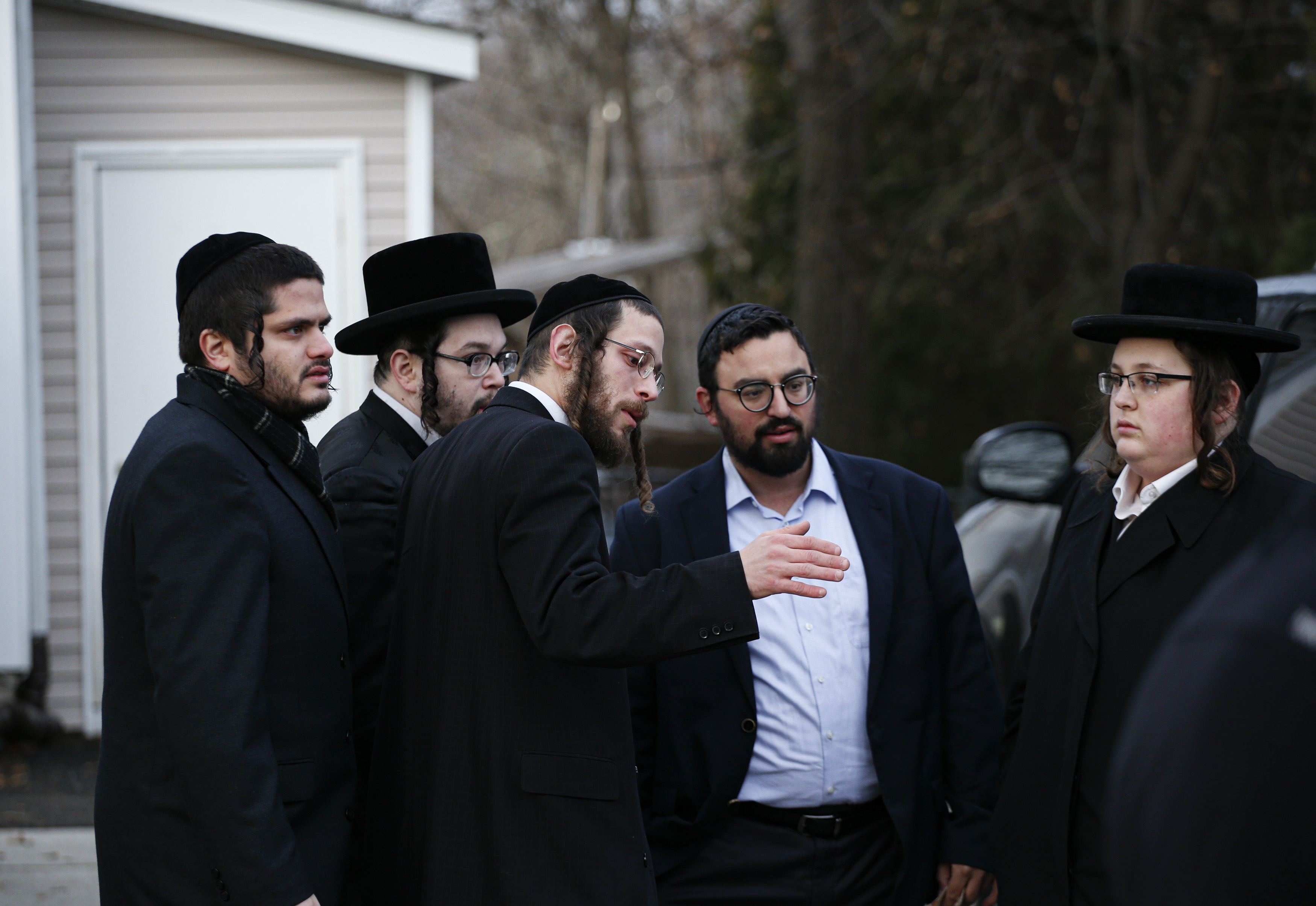Men in Orthodox Jewish attire stand outside a house and talk to one another.