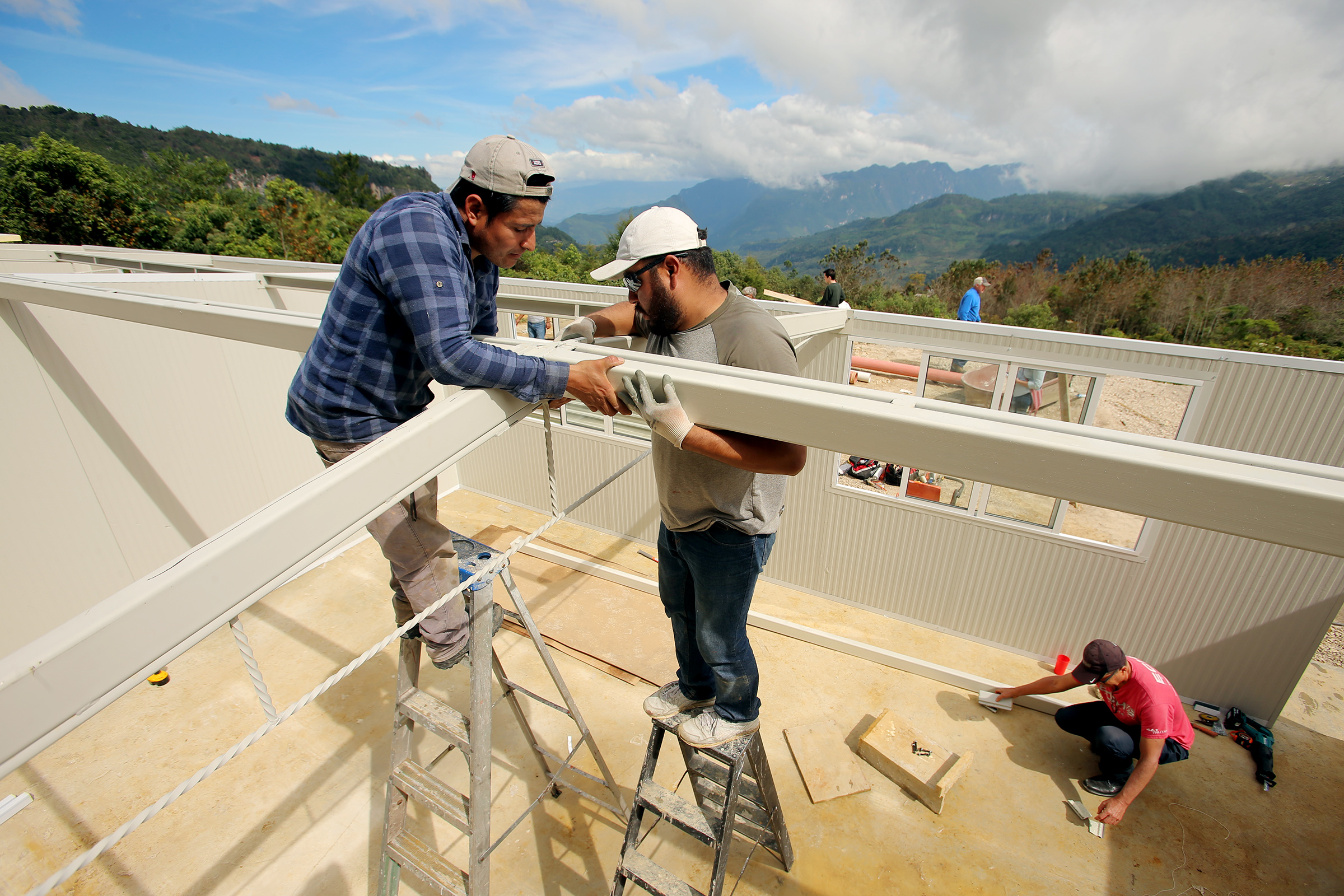 Contractors Alejandro Villar and Antony Villanueva attach roof trusses as they and other workers and volunteers construct a pair of classrooms for kids in San Andres Larrainzar, Mexico, on Friday, Nov. 29, 2019.