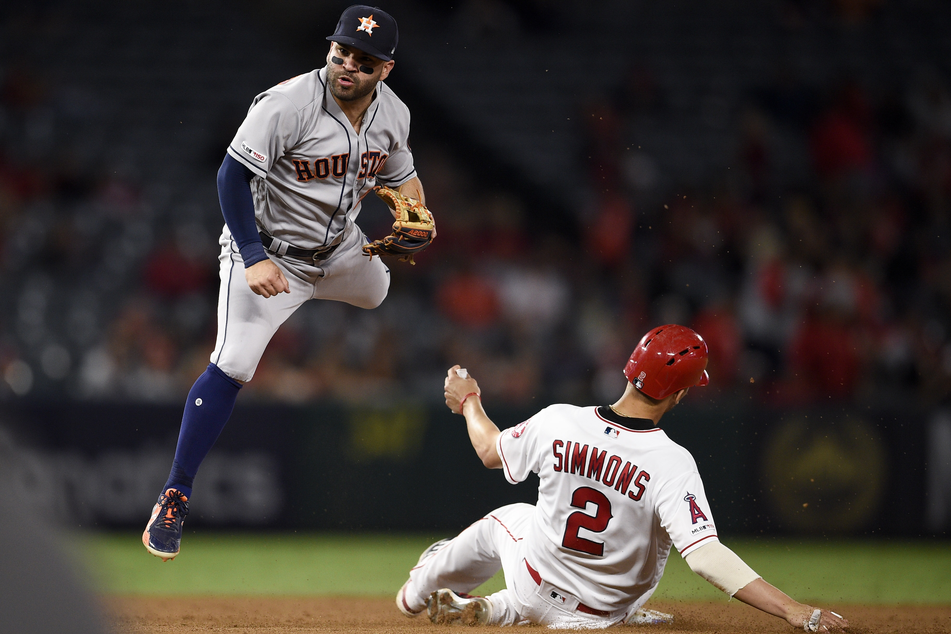 Jose Altuve jumps to avoid the slide of Andrelton Simmons during a force out at second base.  Simmons is wearing the white uniform with red trim.  Altuve is wearing the gray uniform with blue trim.