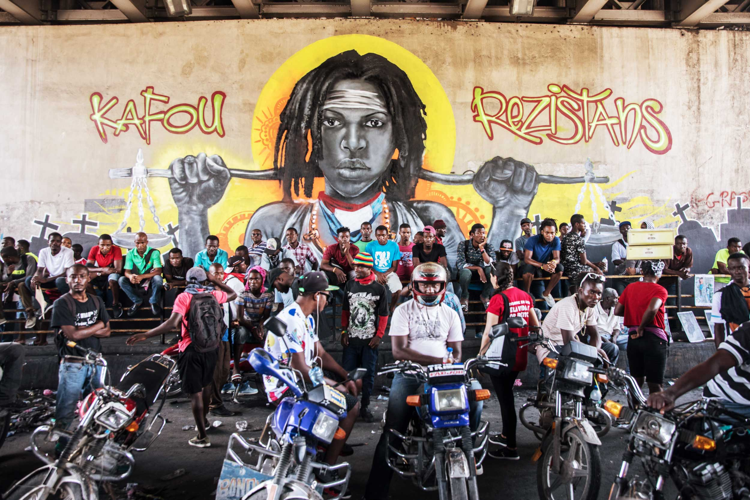 """Haitian demonstrators gather in front of a mural of a person's head and the words, """"Kafou rezistans."""""""