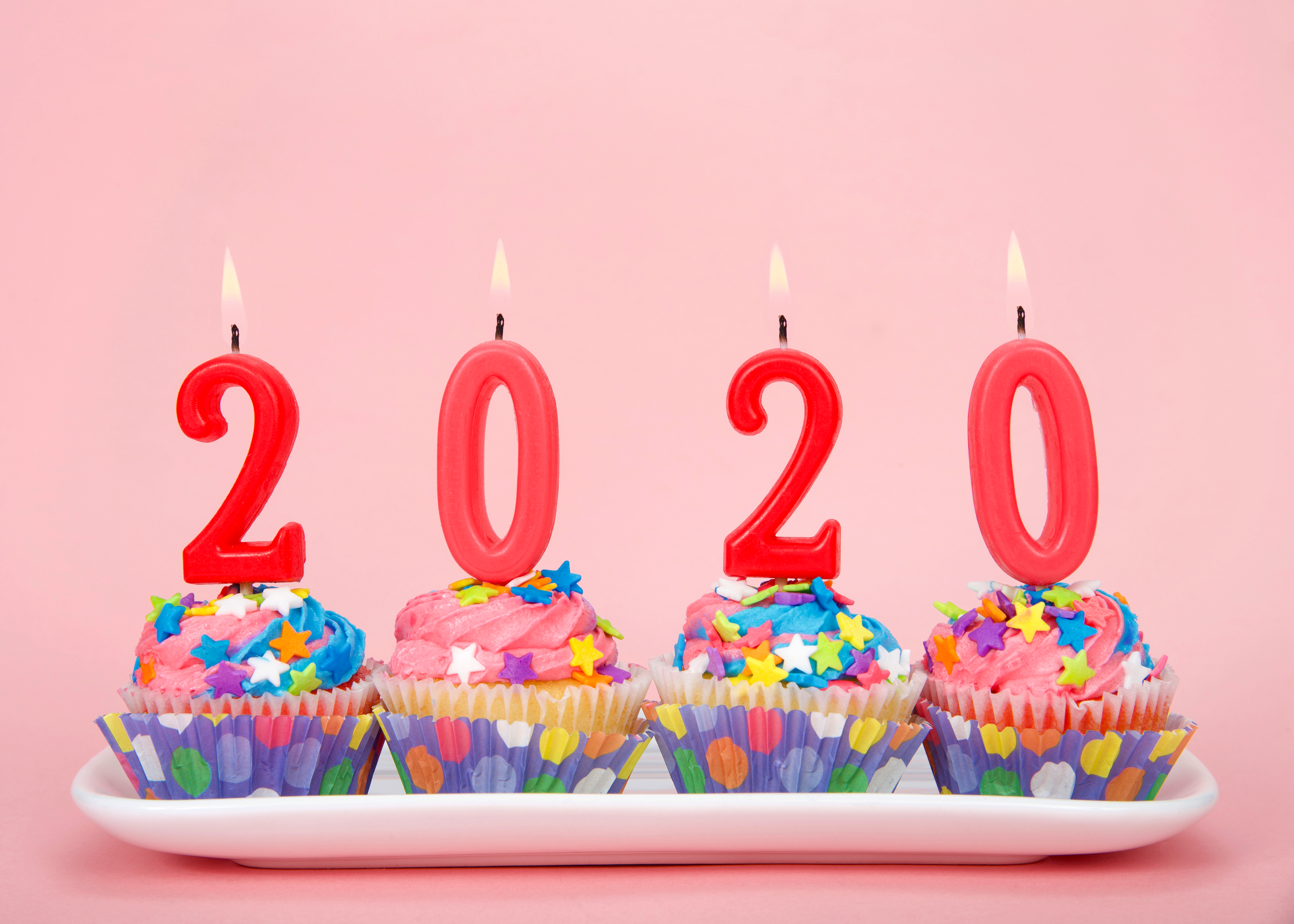 Numbered 2020 candles lit up on top of four colorful cupcakes against a pink background.