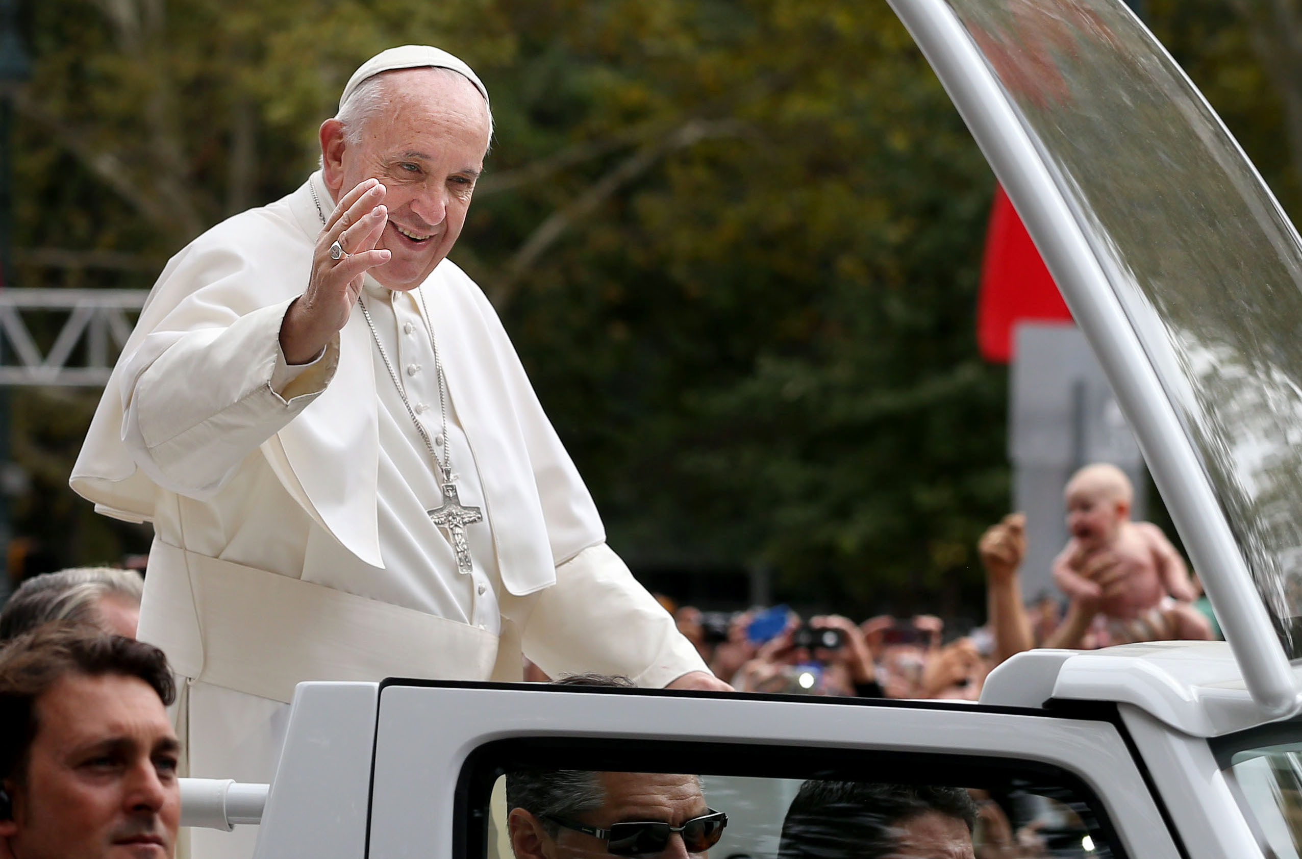 Pope Francis waves to the crowd along Benjamin Franklin Parkway in Philadelphia on Sunday, Sept. 27, 2015.