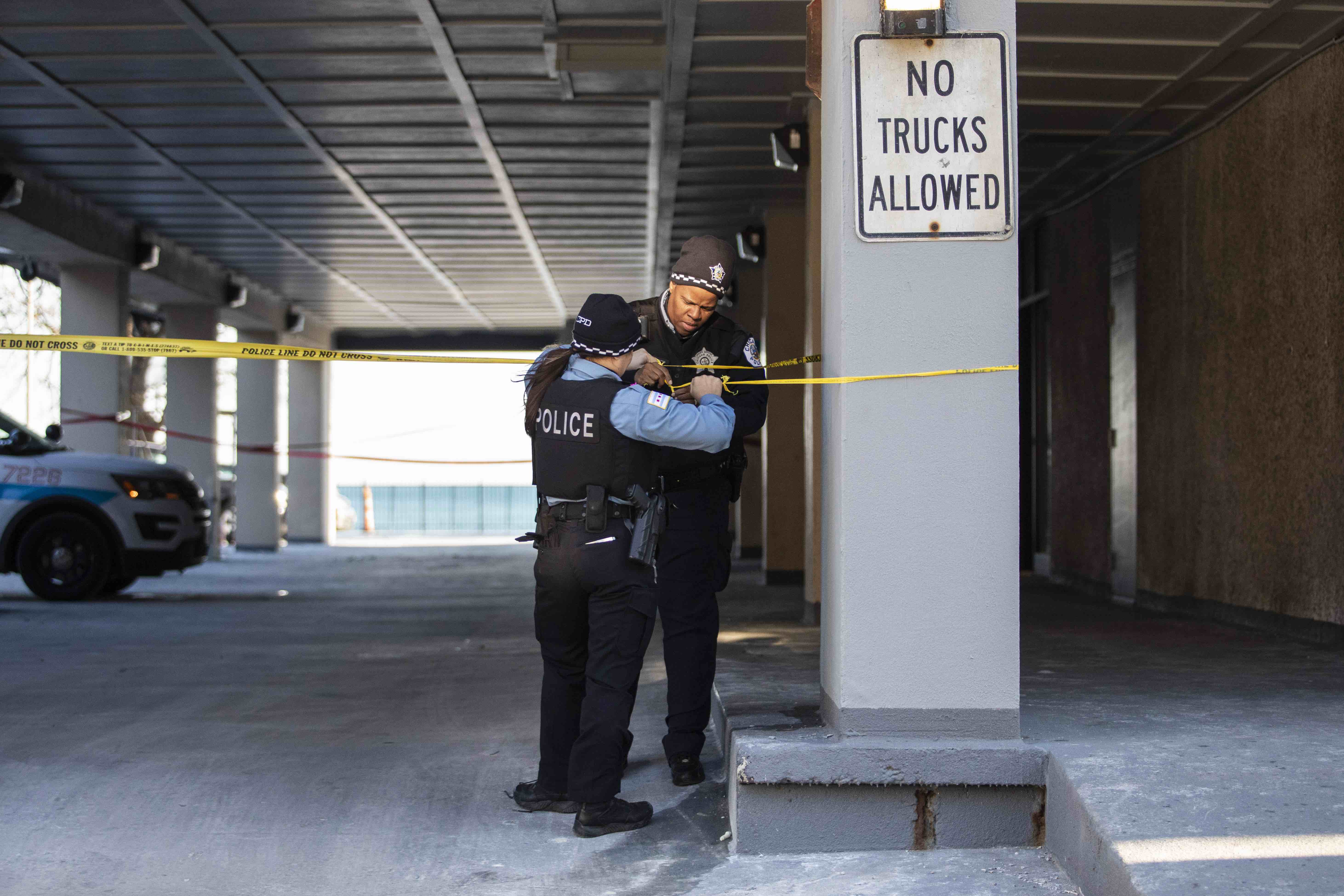 Chicago Police adjust the crime scene tape at a South Shore high-rise apartment building in the 7200 block of South Shore Drive,