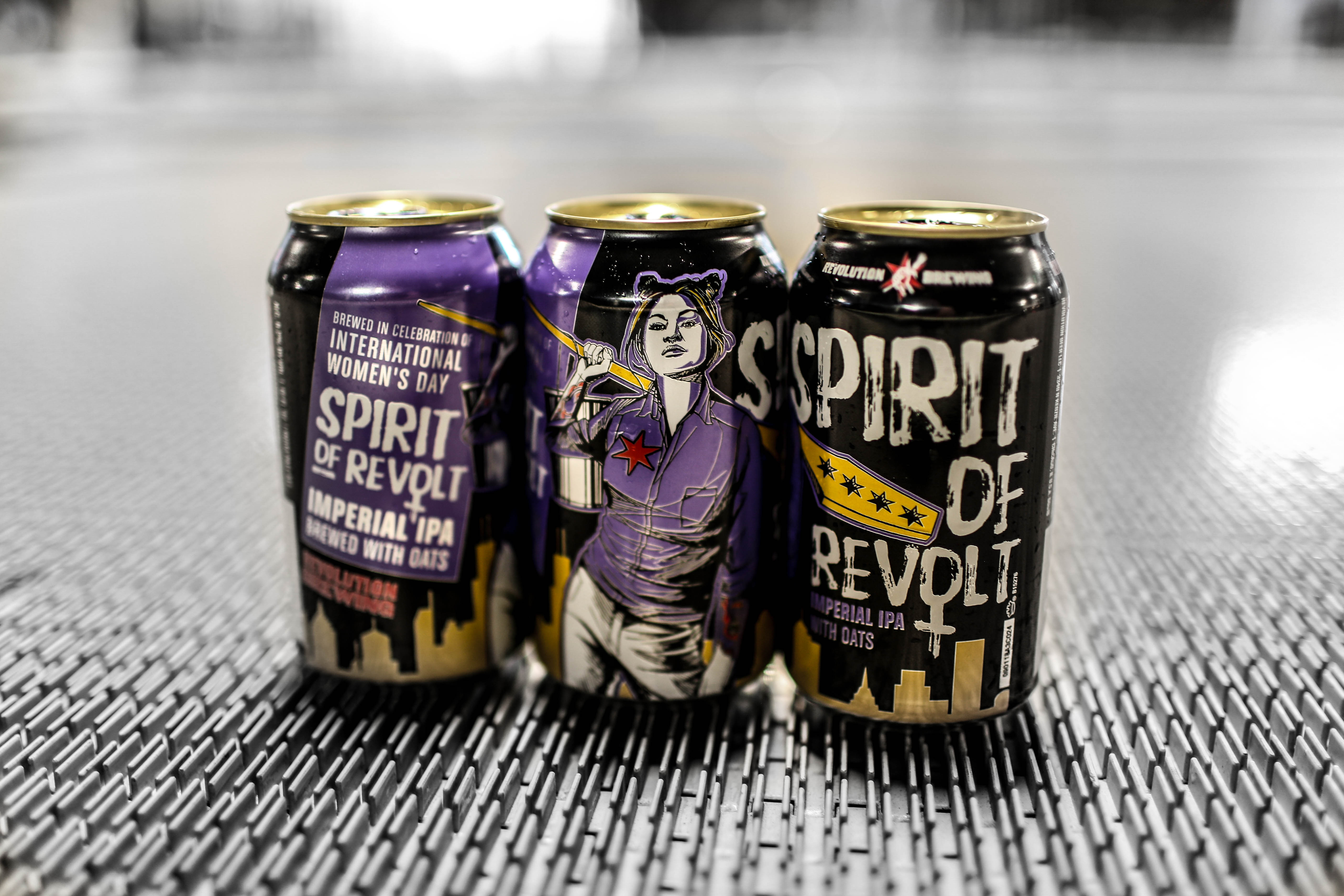 A six-pack of canned beer in black, purple, and white cans.