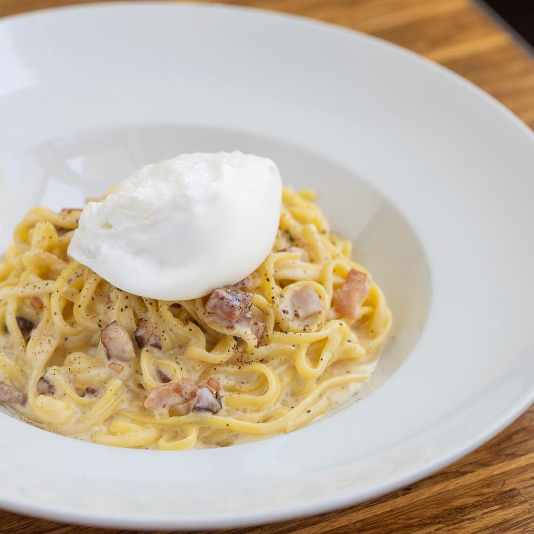 A plate of pasta with burrata on top.