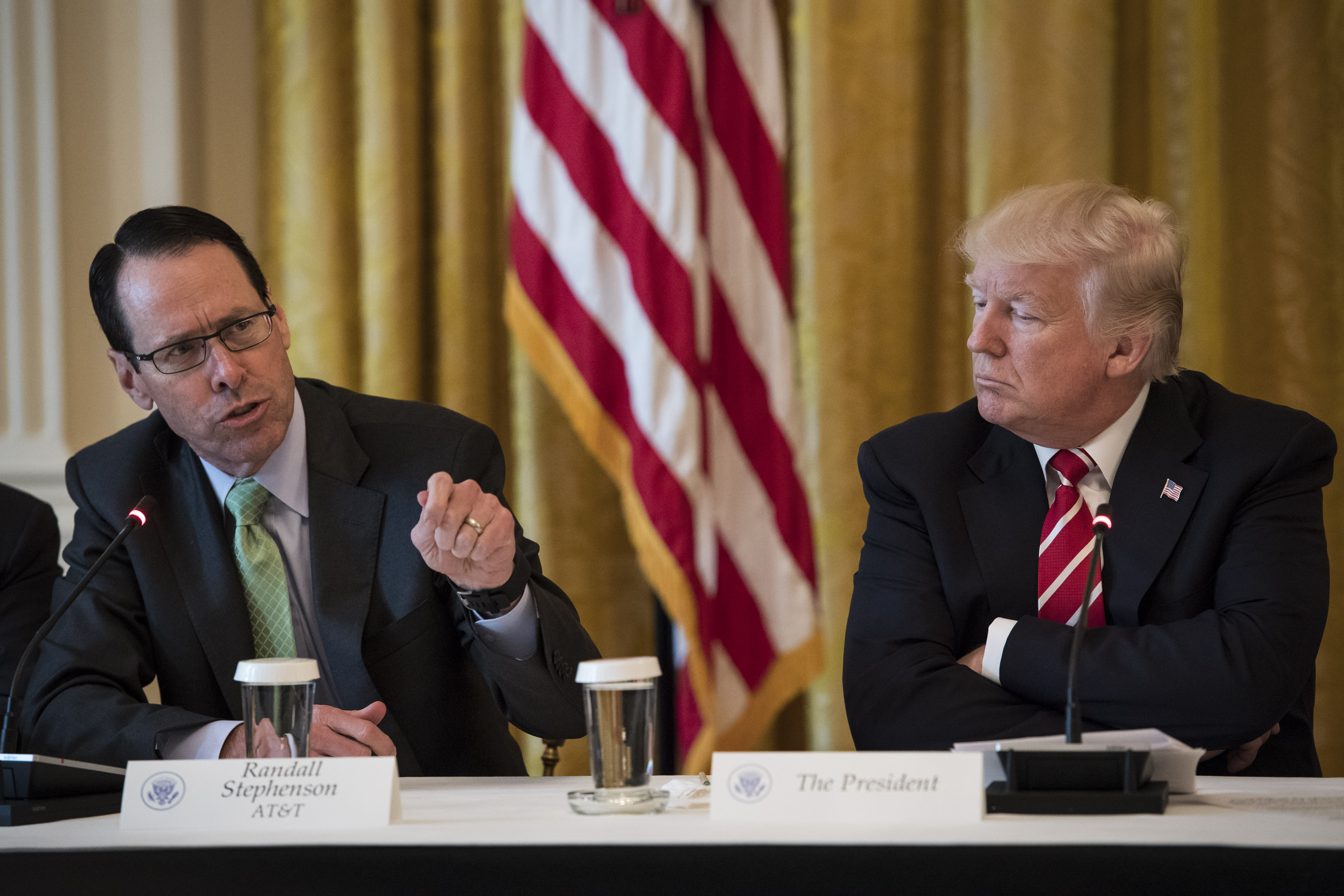 AT&T CEO Randall Stephenson sits and speaks at a conference table while President Donald Trump sits with arms folded and listens.