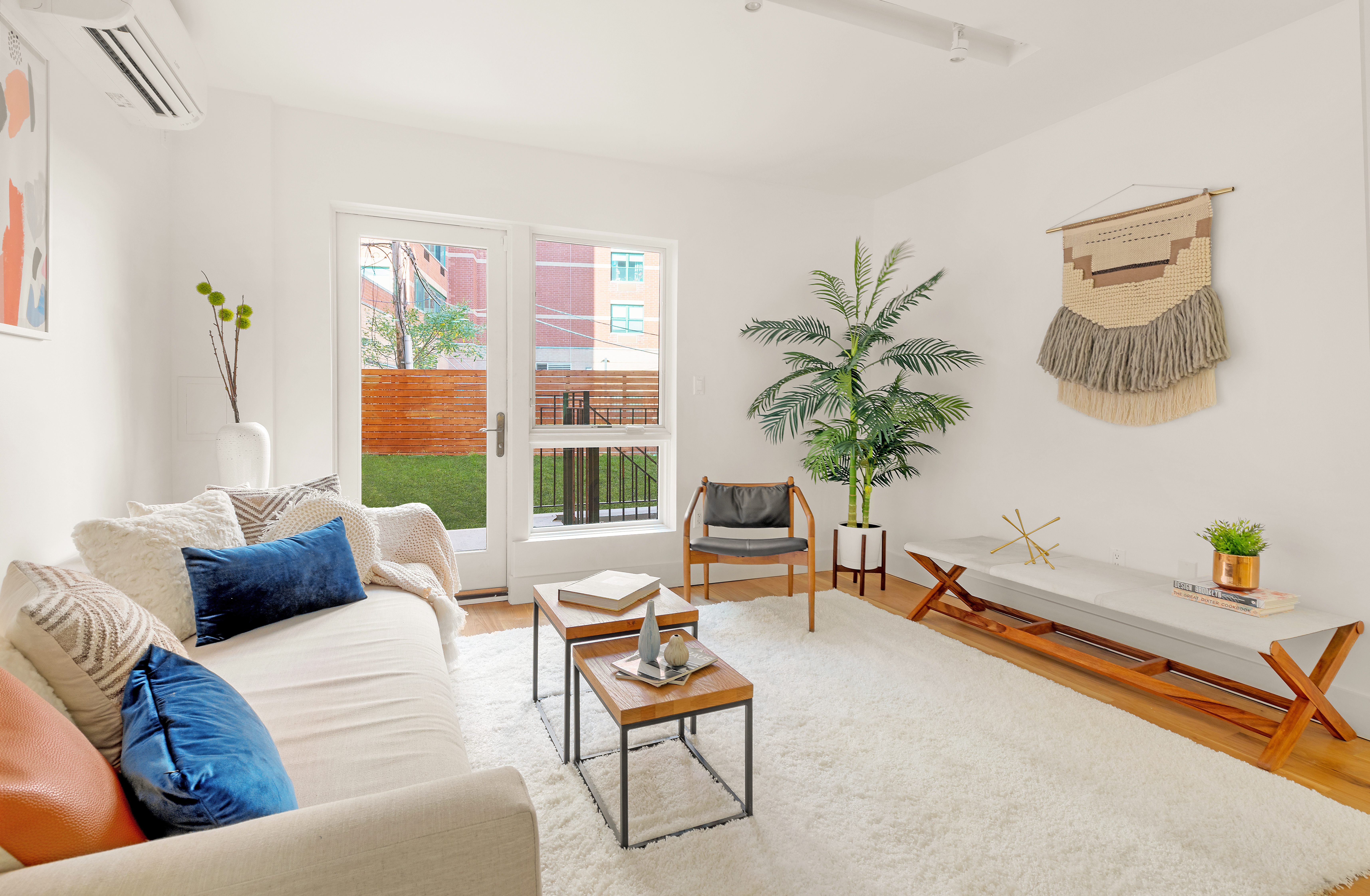 A living room with a white rug, a door that leads to a backyard, a beige couch, two wooden coffee tables, and a planter.