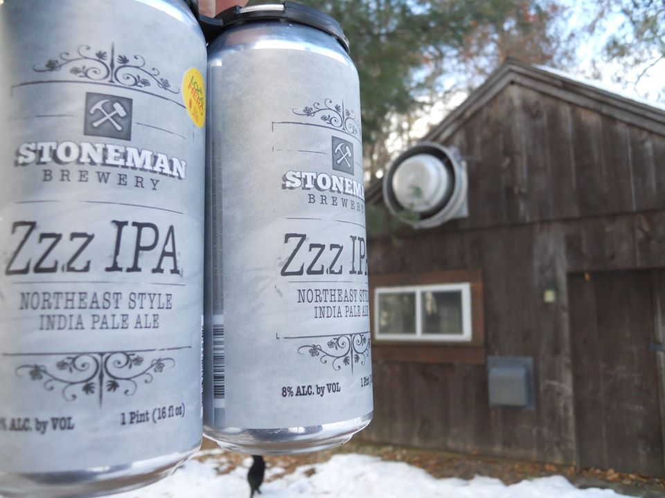 Two cans of beer are held up in front of a small wooden shack. Snow is on the ground.