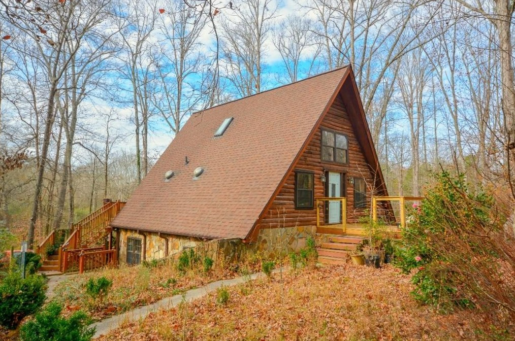 An A-frame cabin in the woods with bare trees all around it.
