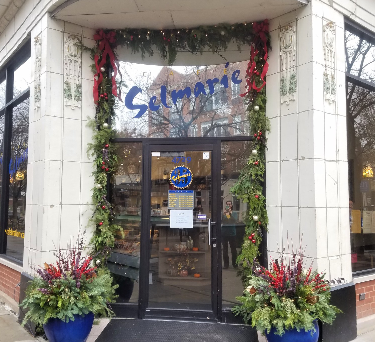 A cafe's door decorated with greenery for Christmas.