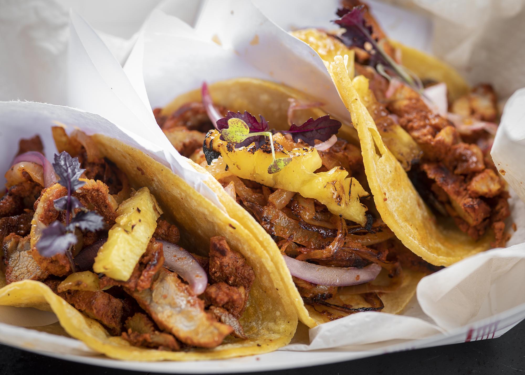 Three tacos on corn tortillas stuffed with al pastor.