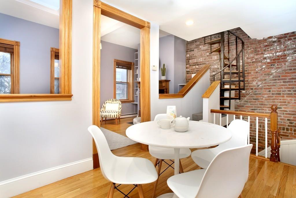 A dining room with a table and chairs amid staircases.